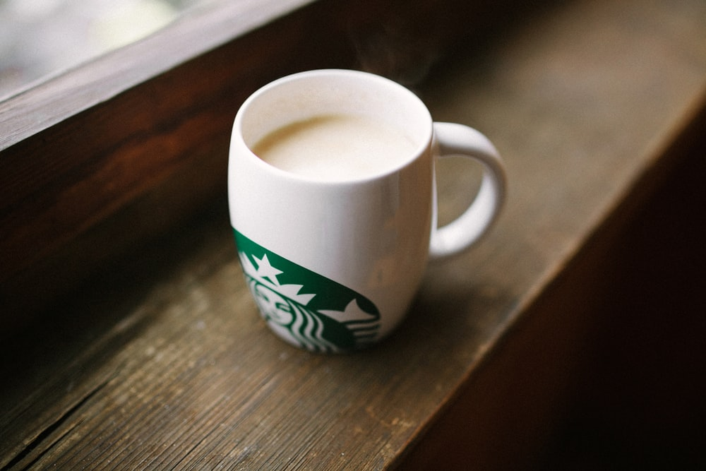 photo of white Starbucks mug on brown wooden surface