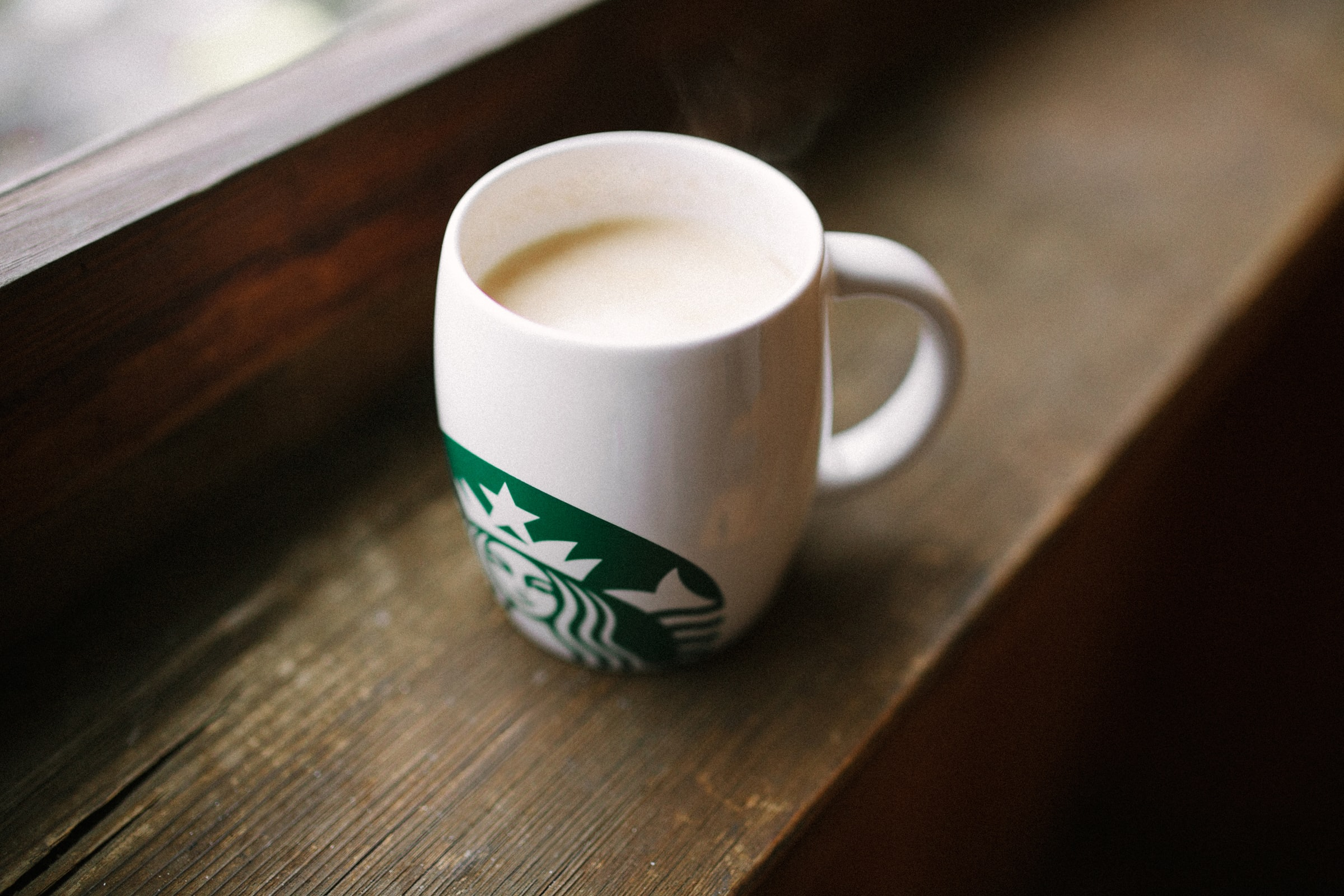 photo of white Starbucks mug on brown wooden surface