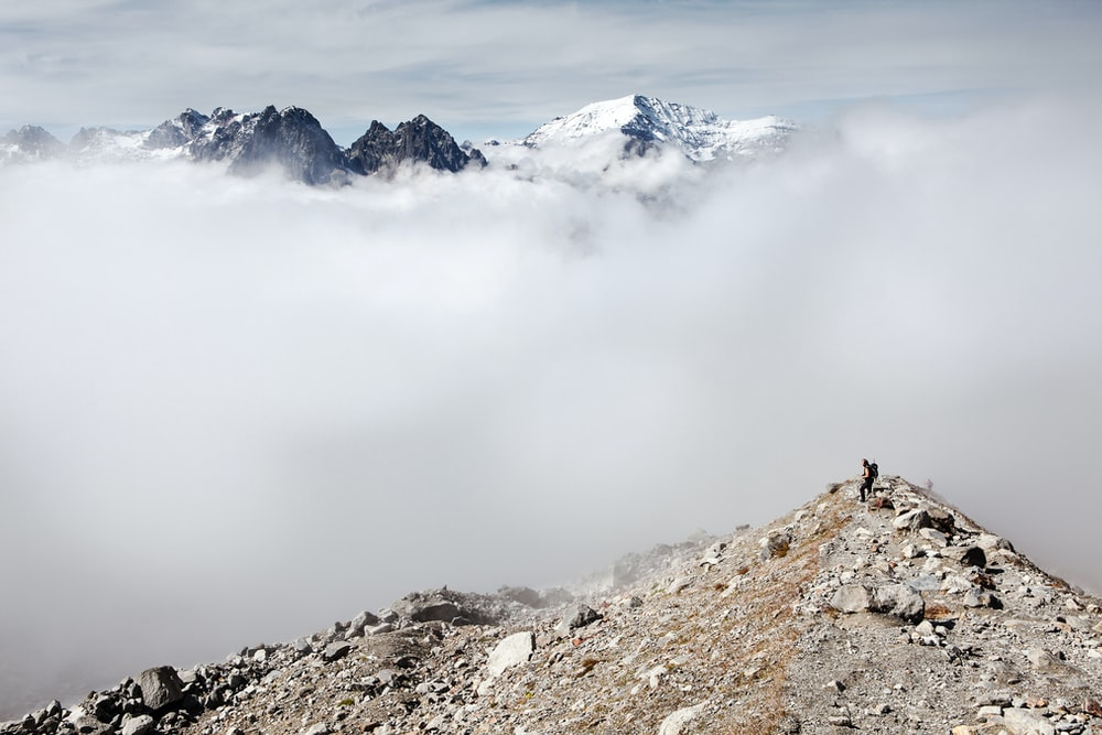 person standing on peak front of white clouds and ice-capped mountain