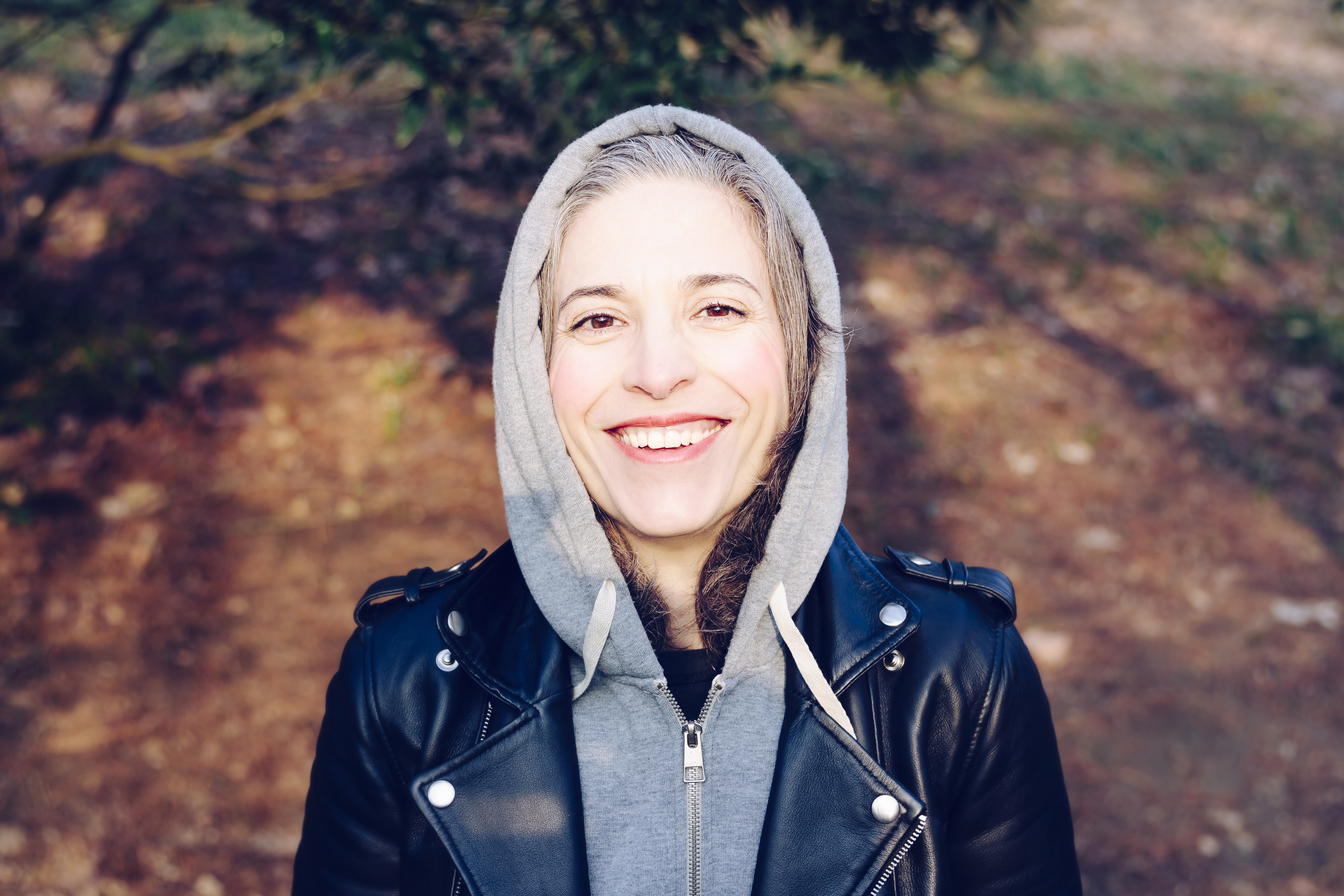 A smiling woman in a gray hooded sweatshirt and leather jacket outside in San Sebastián
