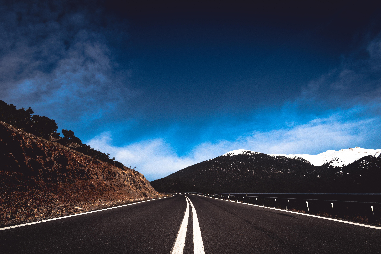road near mountain under blue sky