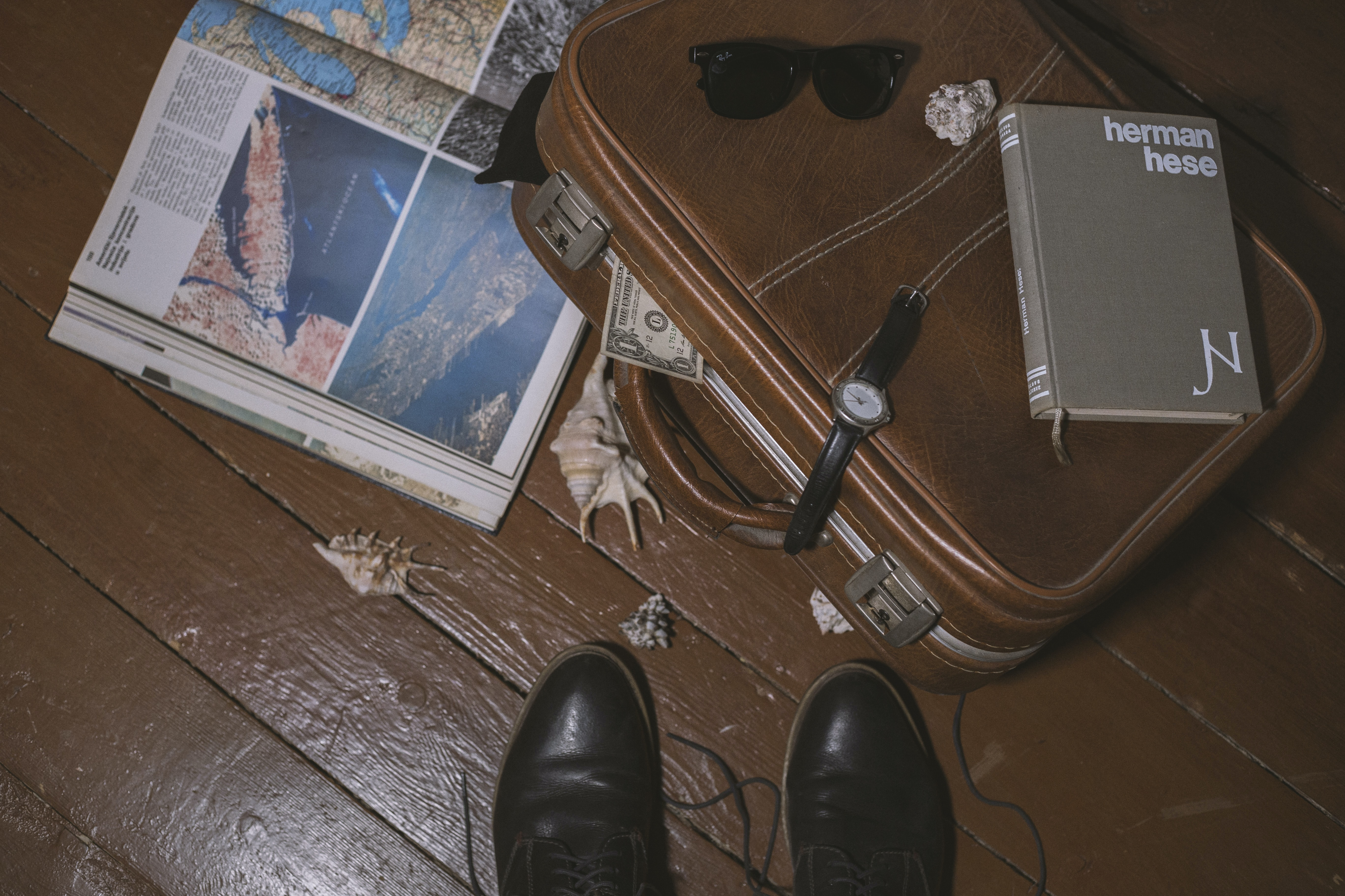 An overhead view of a person's shoes next to a leather suitcase with a book on it and a tourist guide under it