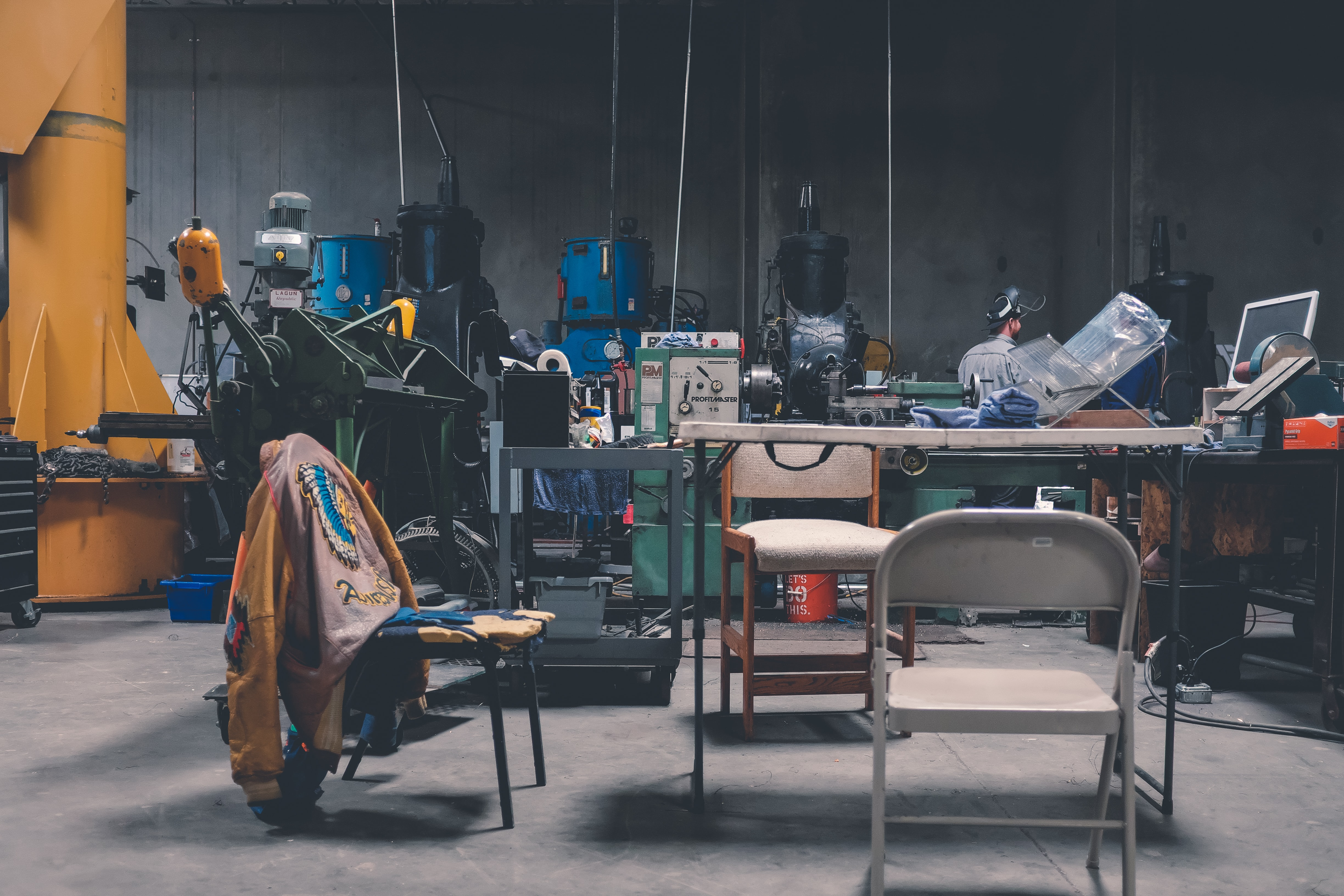 A man working in a messy workshop with a table, chairs and various machines