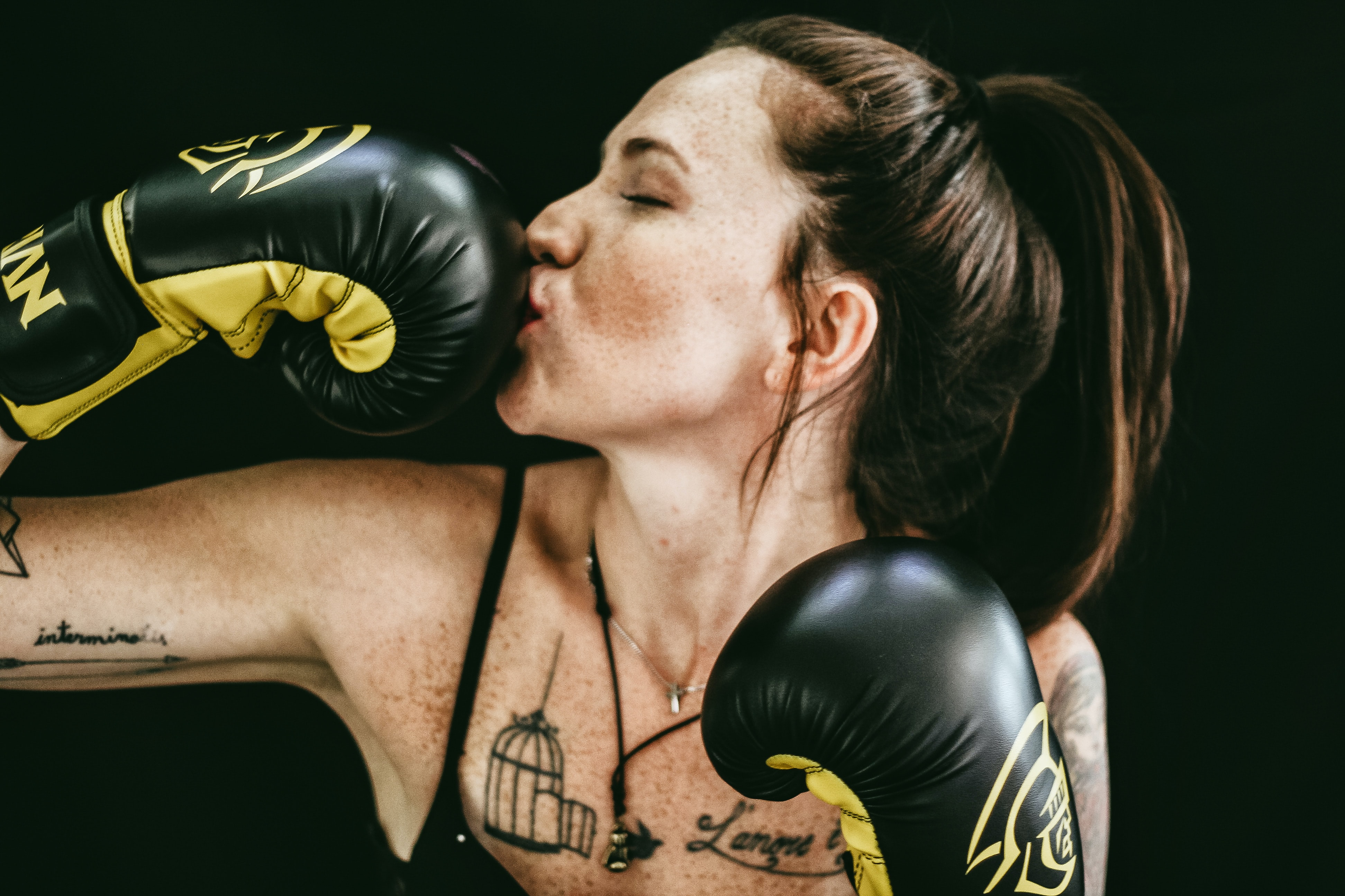 A young woman in black boxing gloves kissing one of her gloves