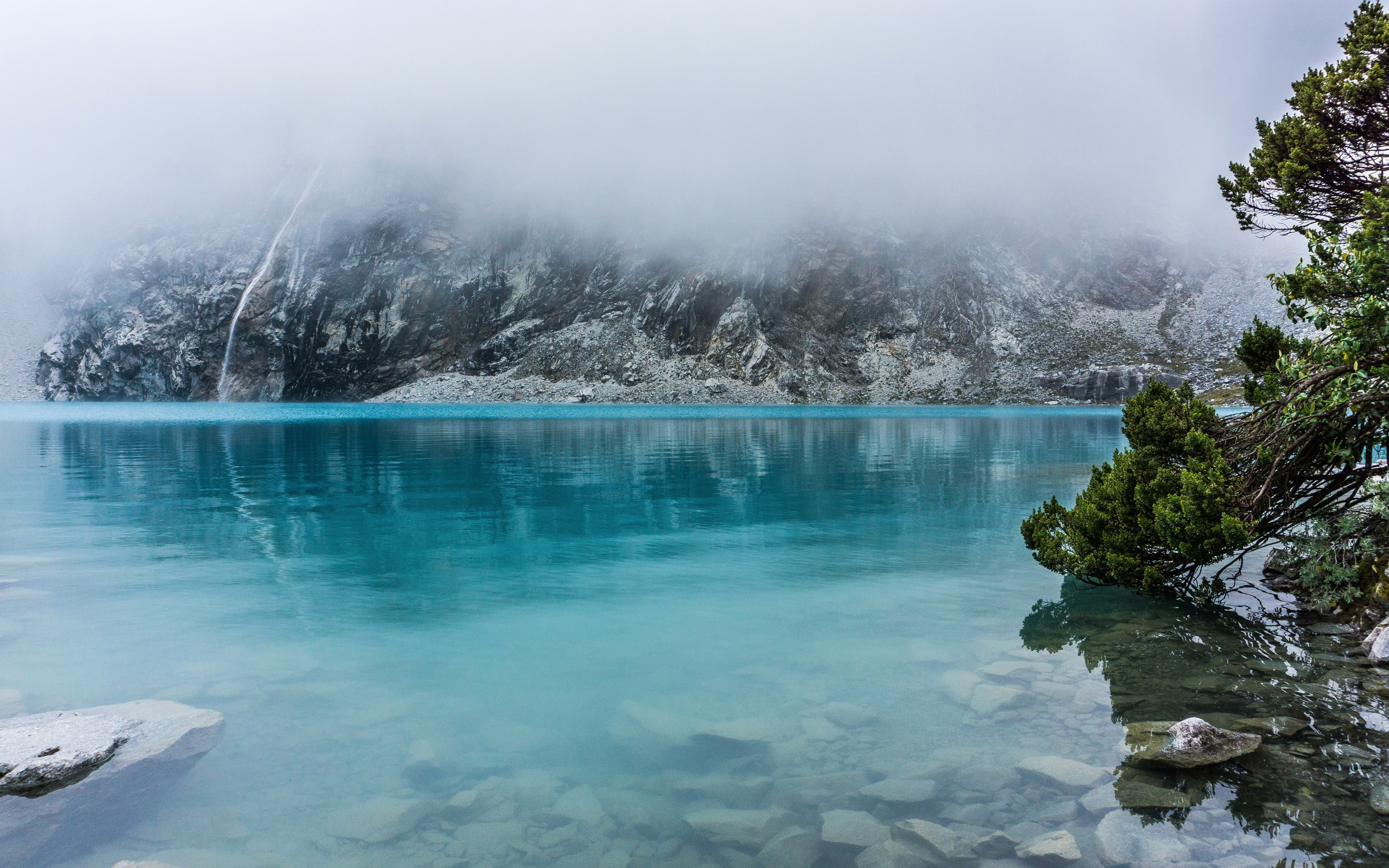 Foggy mountains surrounded by crystal blue water below