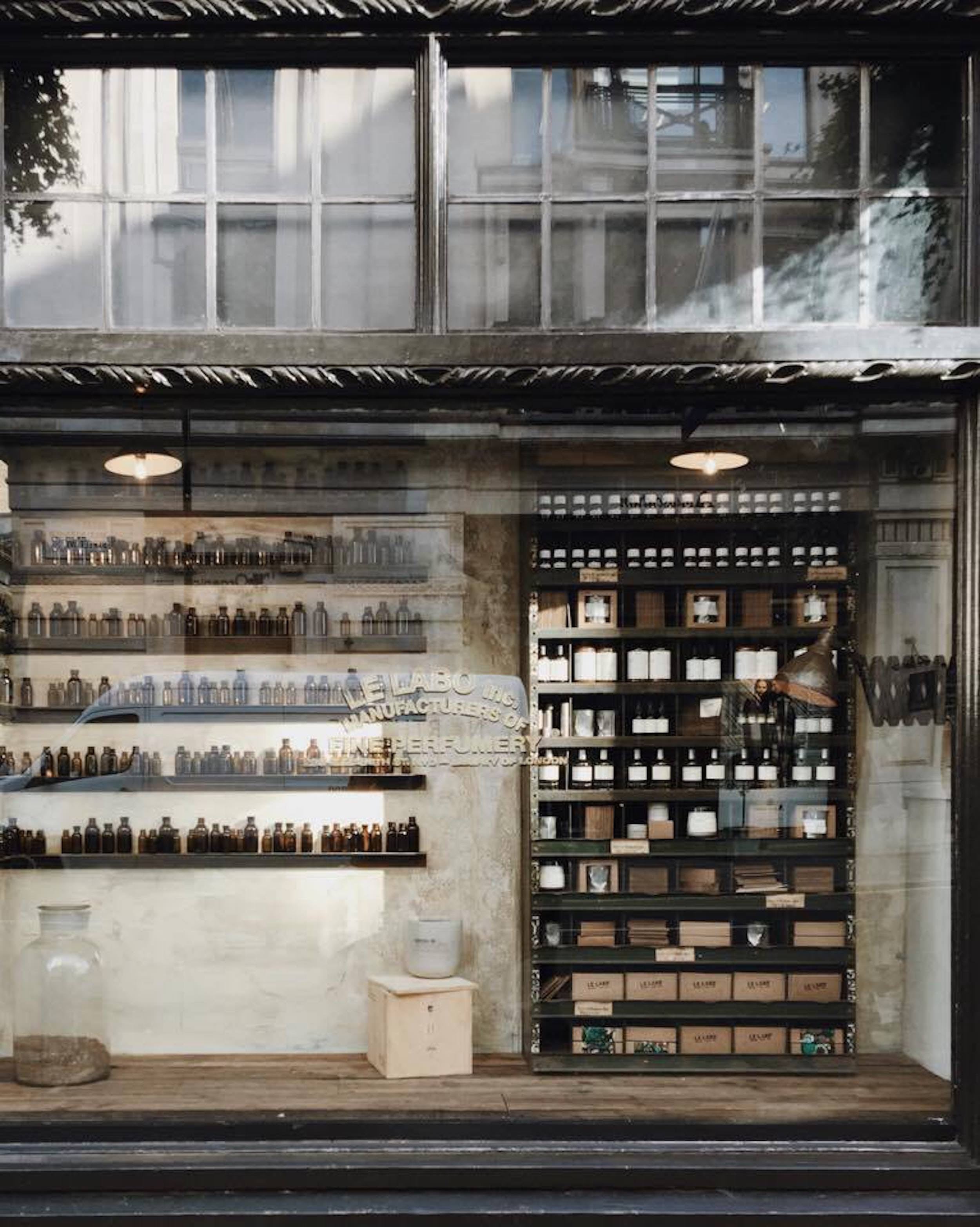 The front view of a shop with glass windows containing glass bottles and a shelf in london.