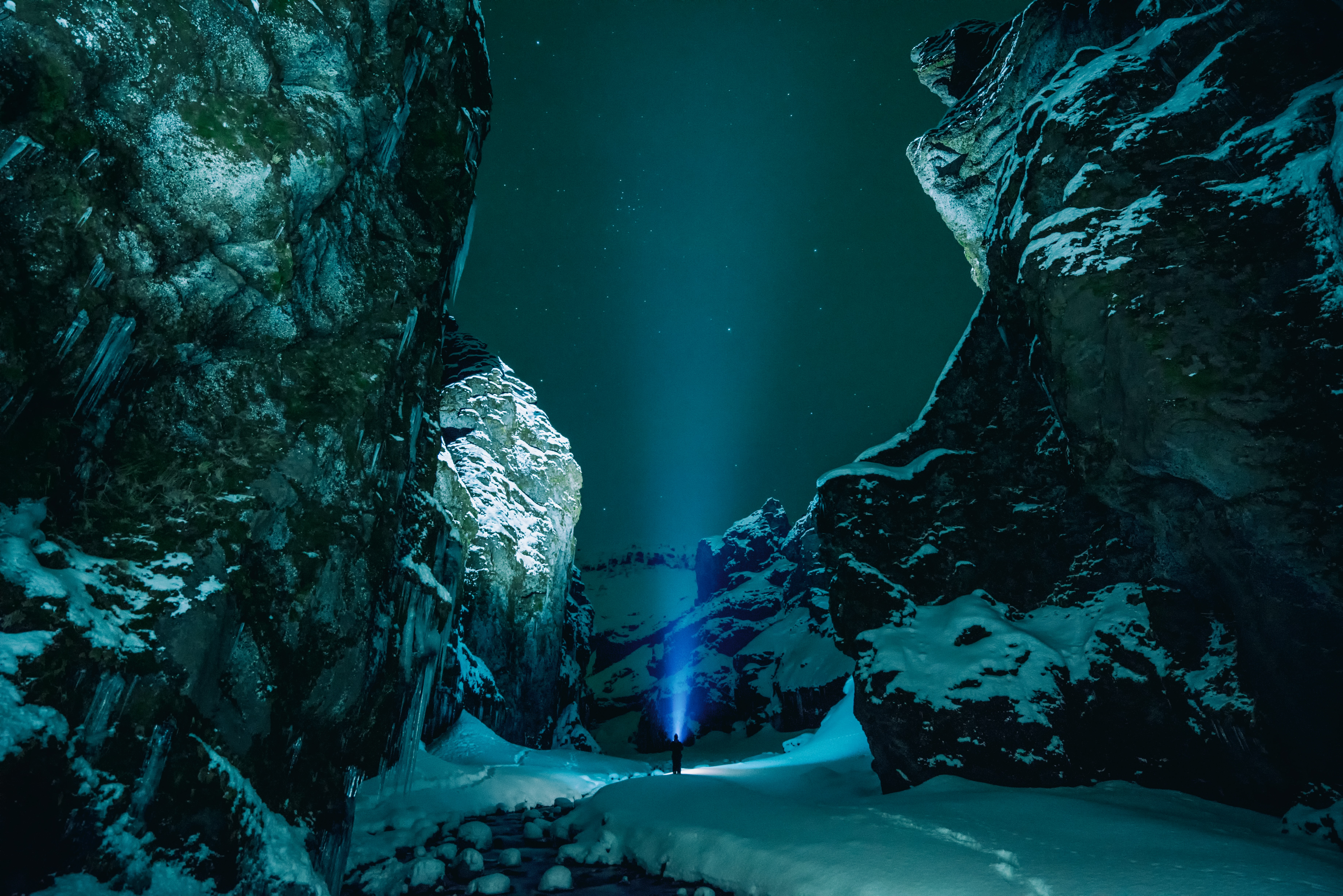 A blue spotlight put onto the starlit sky at the bottom of rock formations in Stakkholtsgjá, Iceland