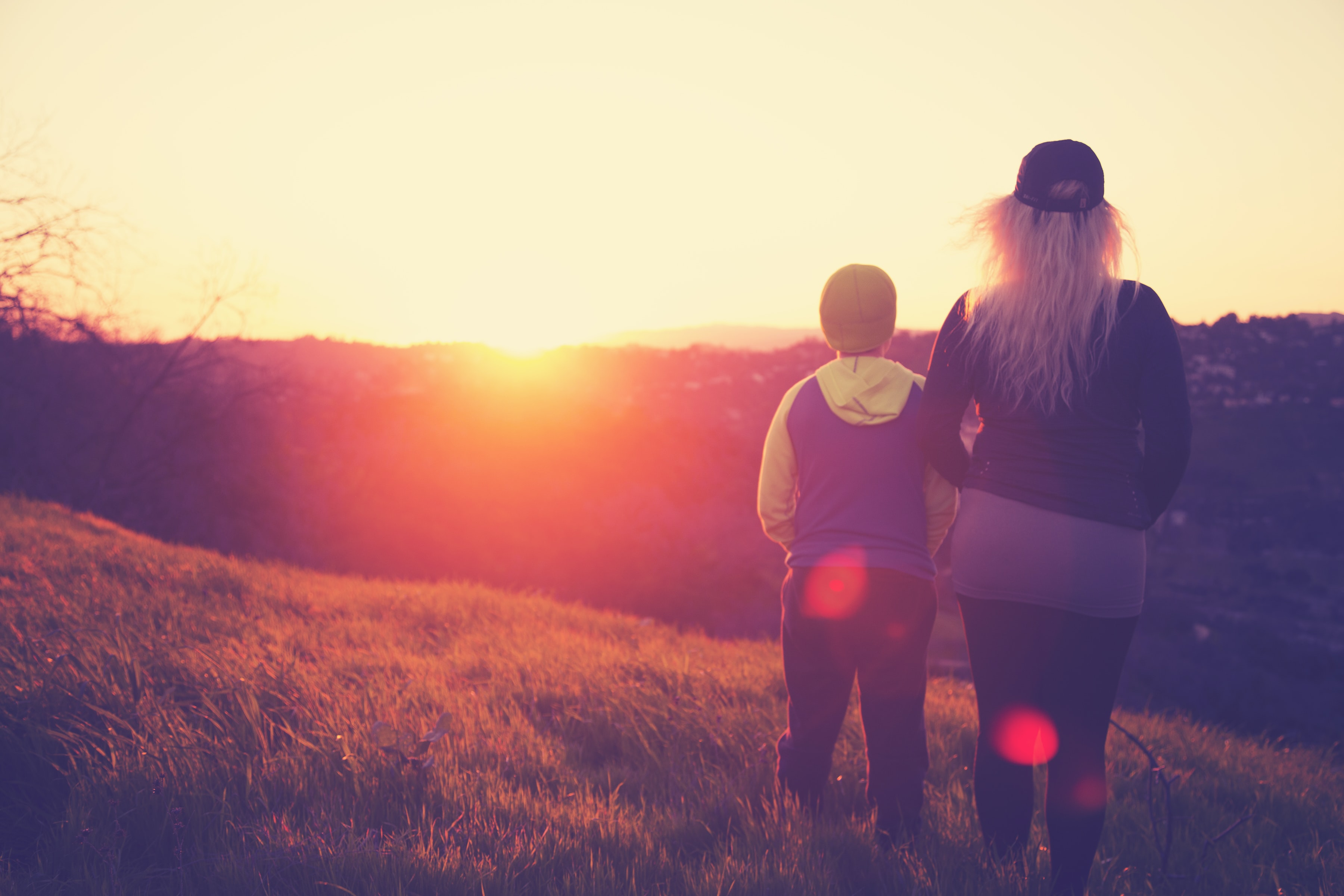 A young boy and a lady standing on a hill in Los Angeles watching the sunset