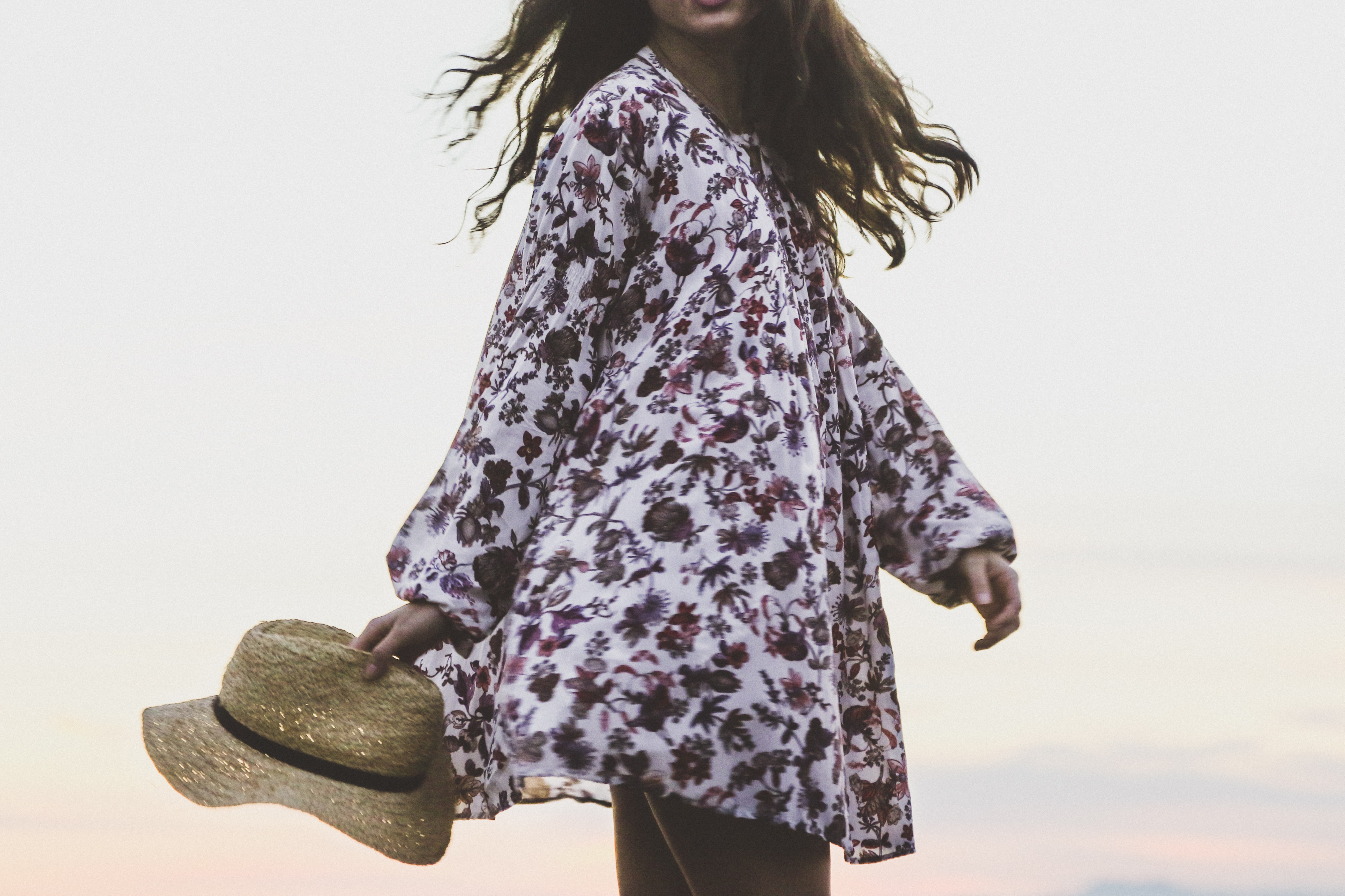 woman wearing white and brown floral long-sleeved shirt while holding brown fedora hat