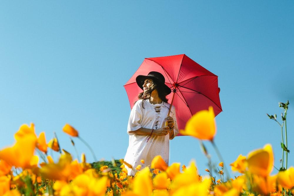 woman in white dress under red umbrella