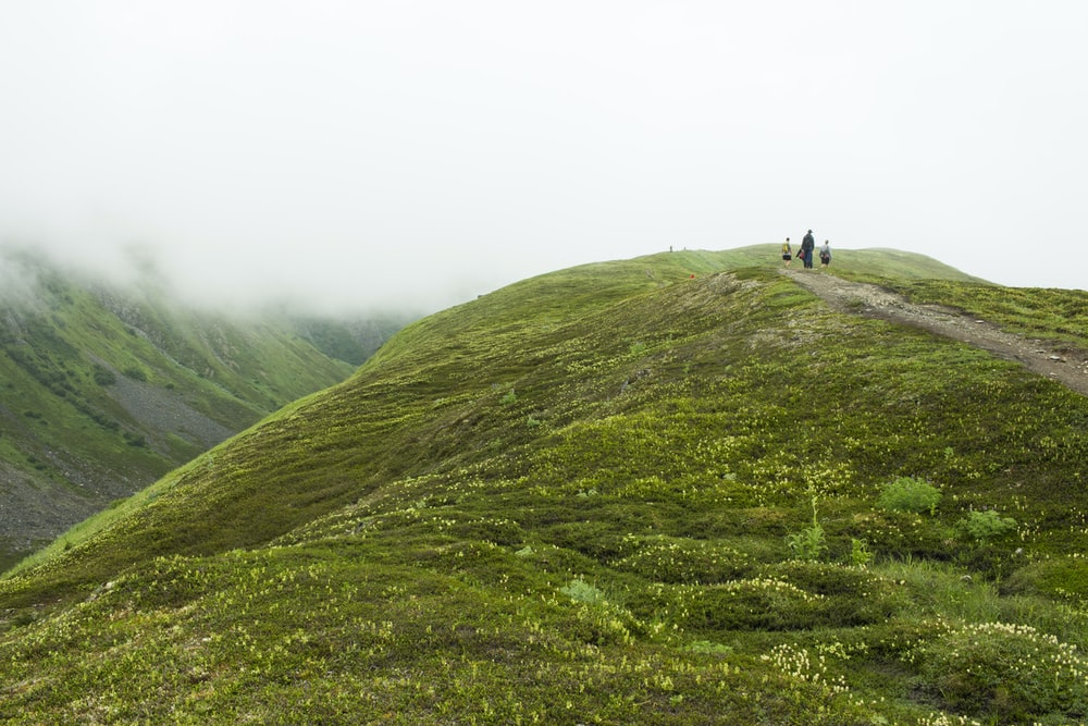 three people standing on top of hill