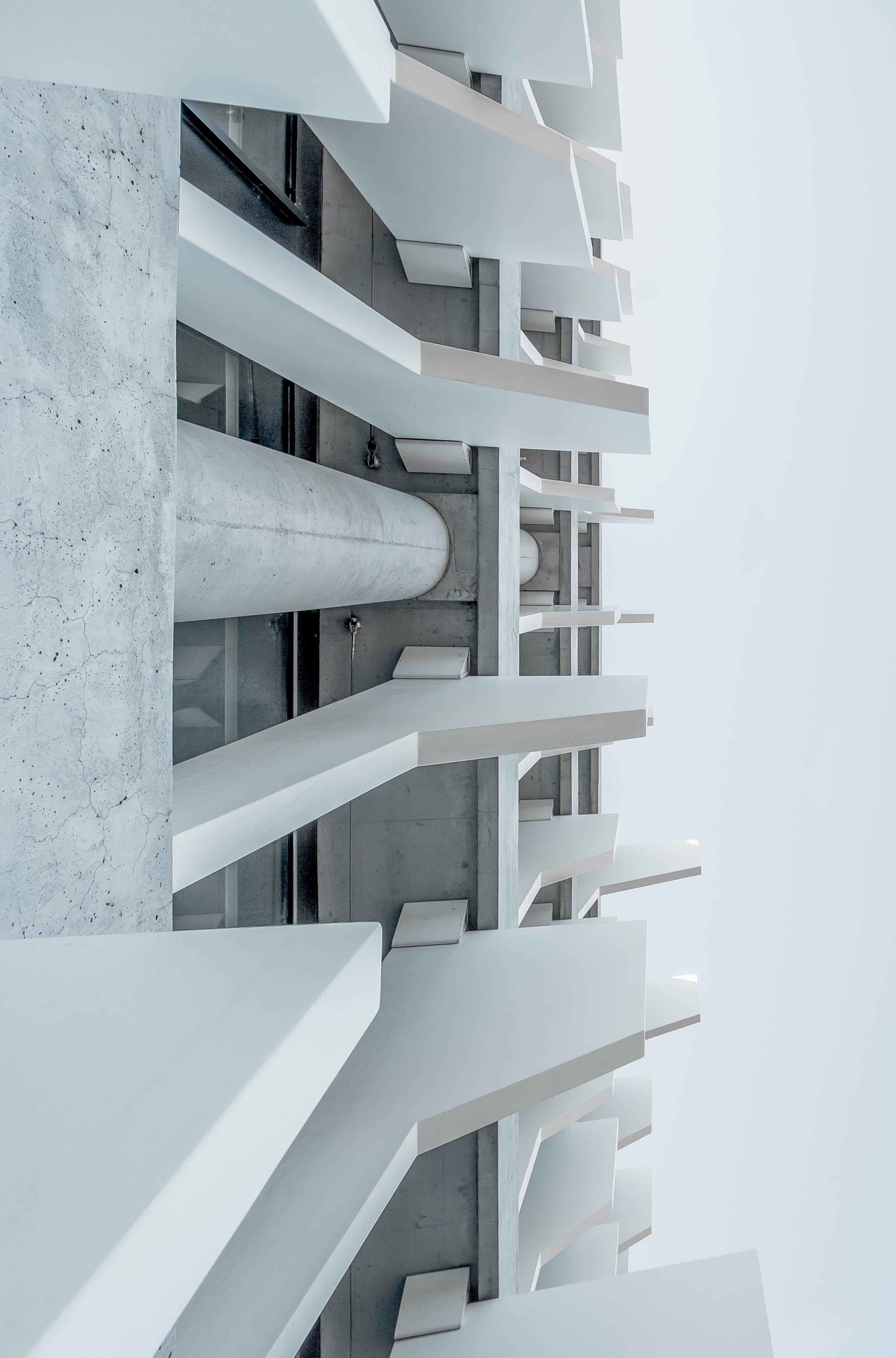 A low-angle shot of a white concrete building facade in Madrid