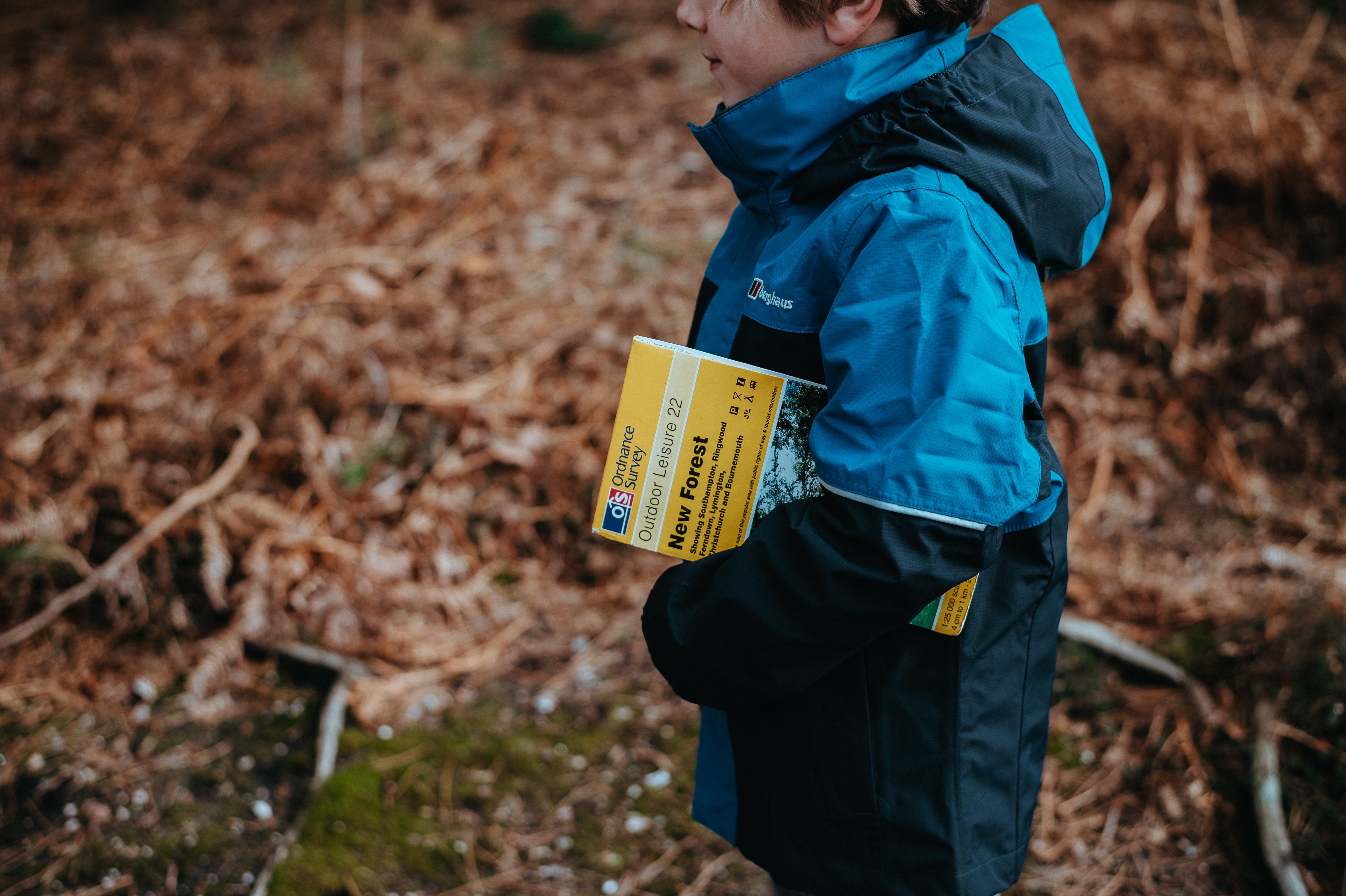 boy carrying book standing on ground during daytime
