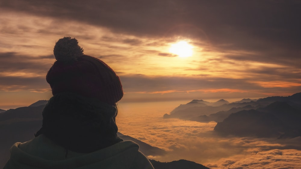 person in red knit cap leaning on sea of clouds