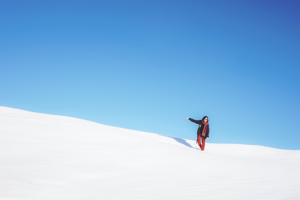 woman standing on white snow field during daytime
