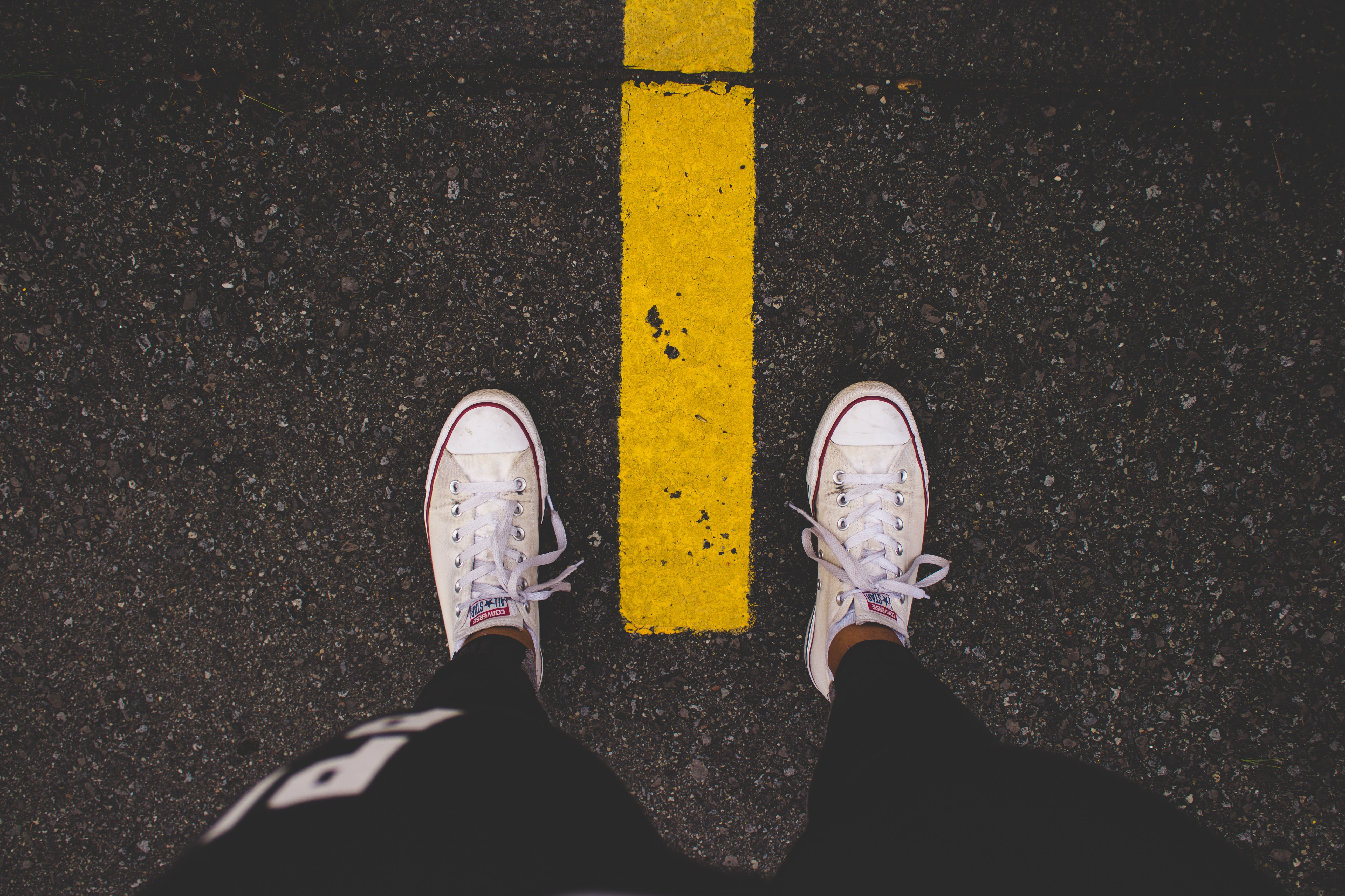 A man staring down at his shoes, each on one side of the yellow street line