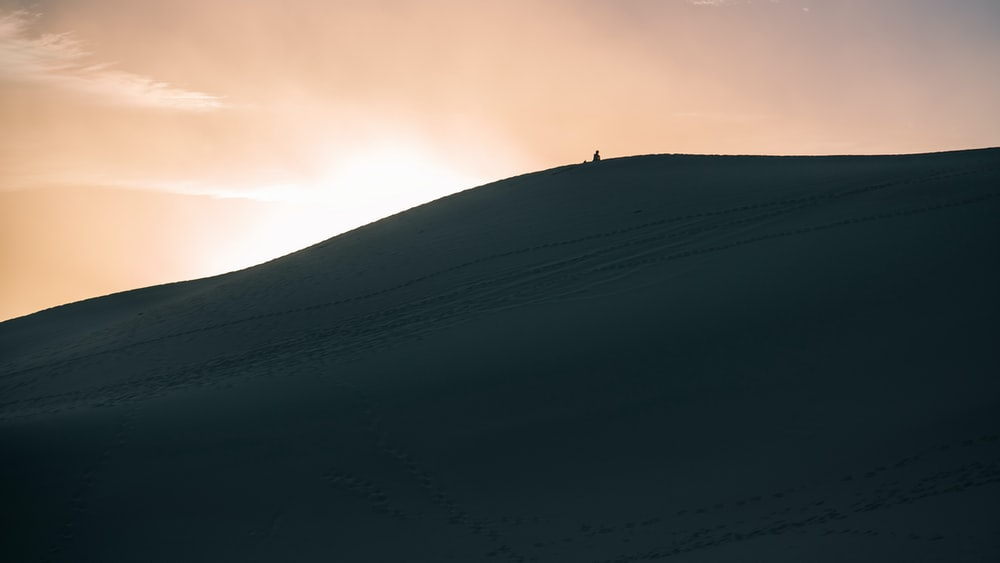 person walking in dune sand