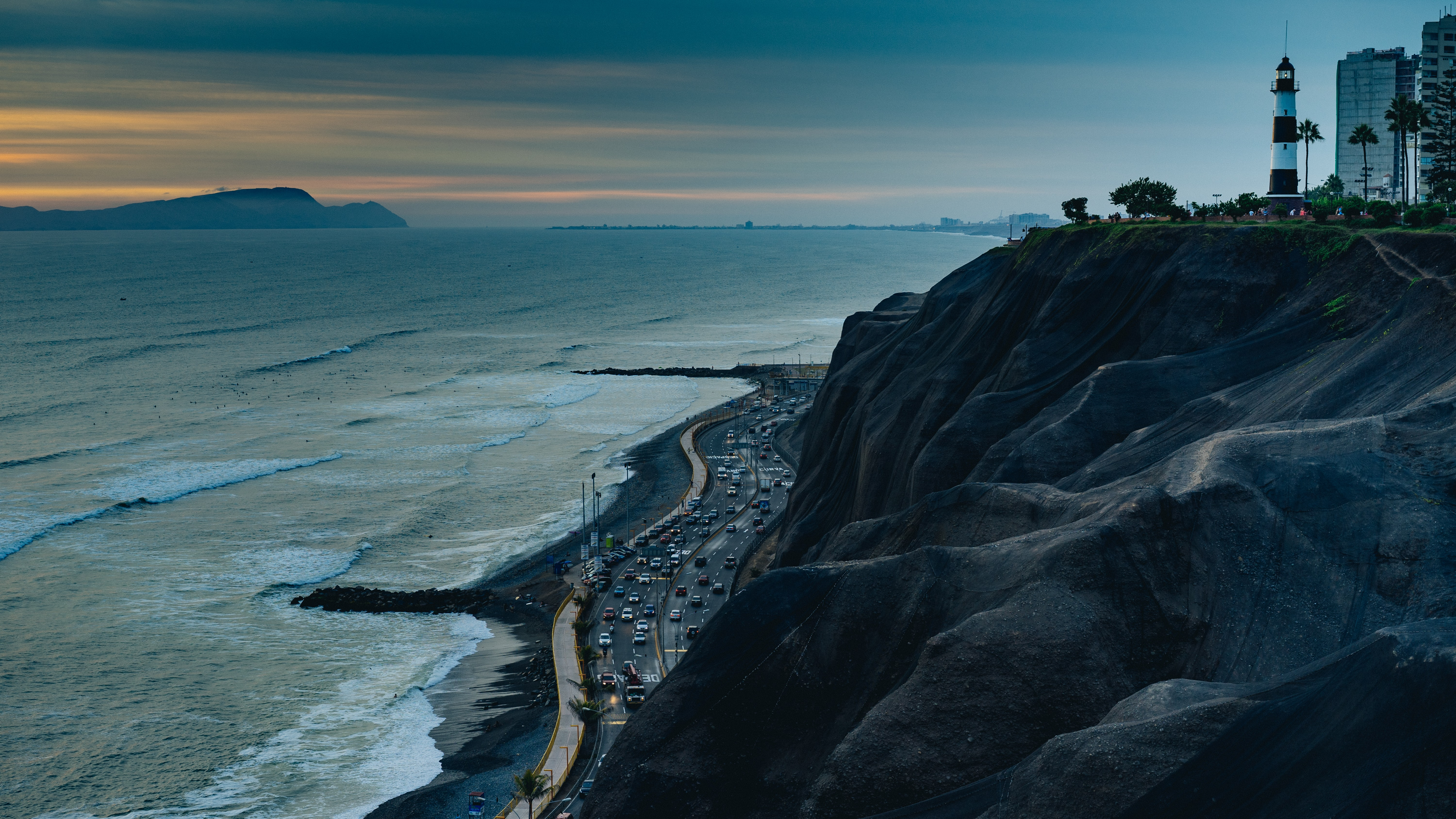 La Marina Lighthouse in Miraflores Peru standing upon a rocky cliff during sunset as waves crash on the shoreline