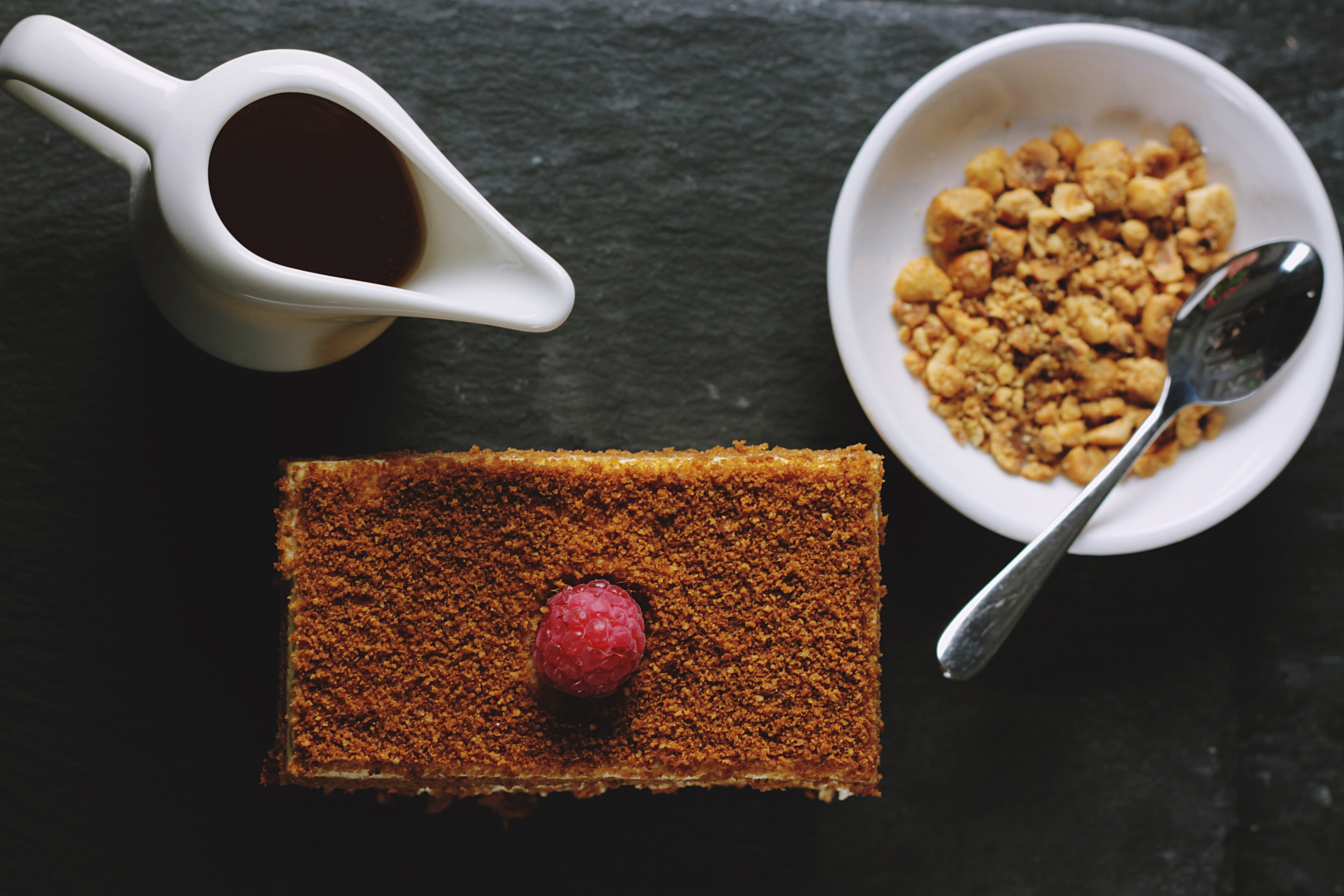 Flat lay of breakfast cake, syrup, and hazelnuts