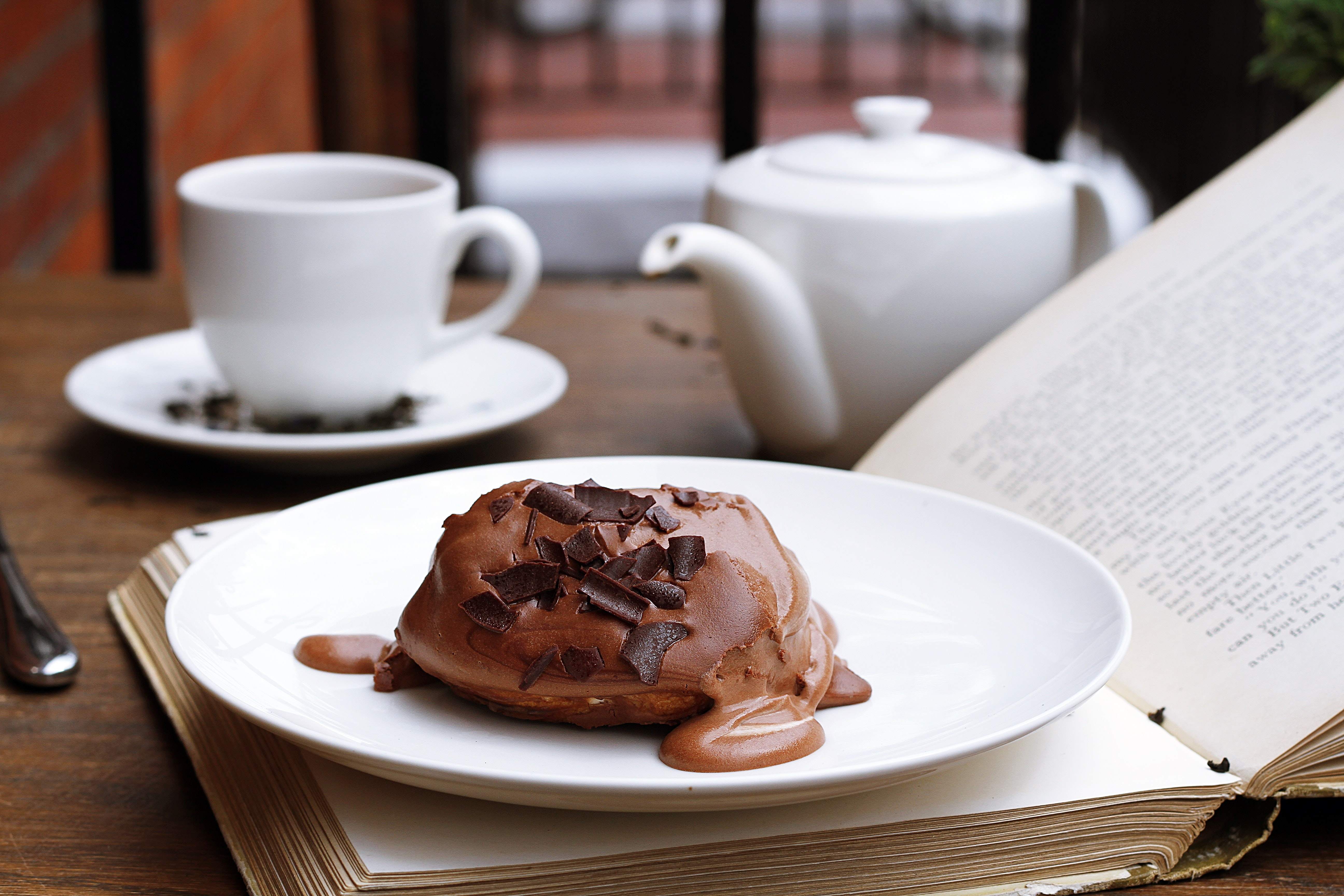 Chocolate dessert on an open book with a tea pot and tea cup in the background