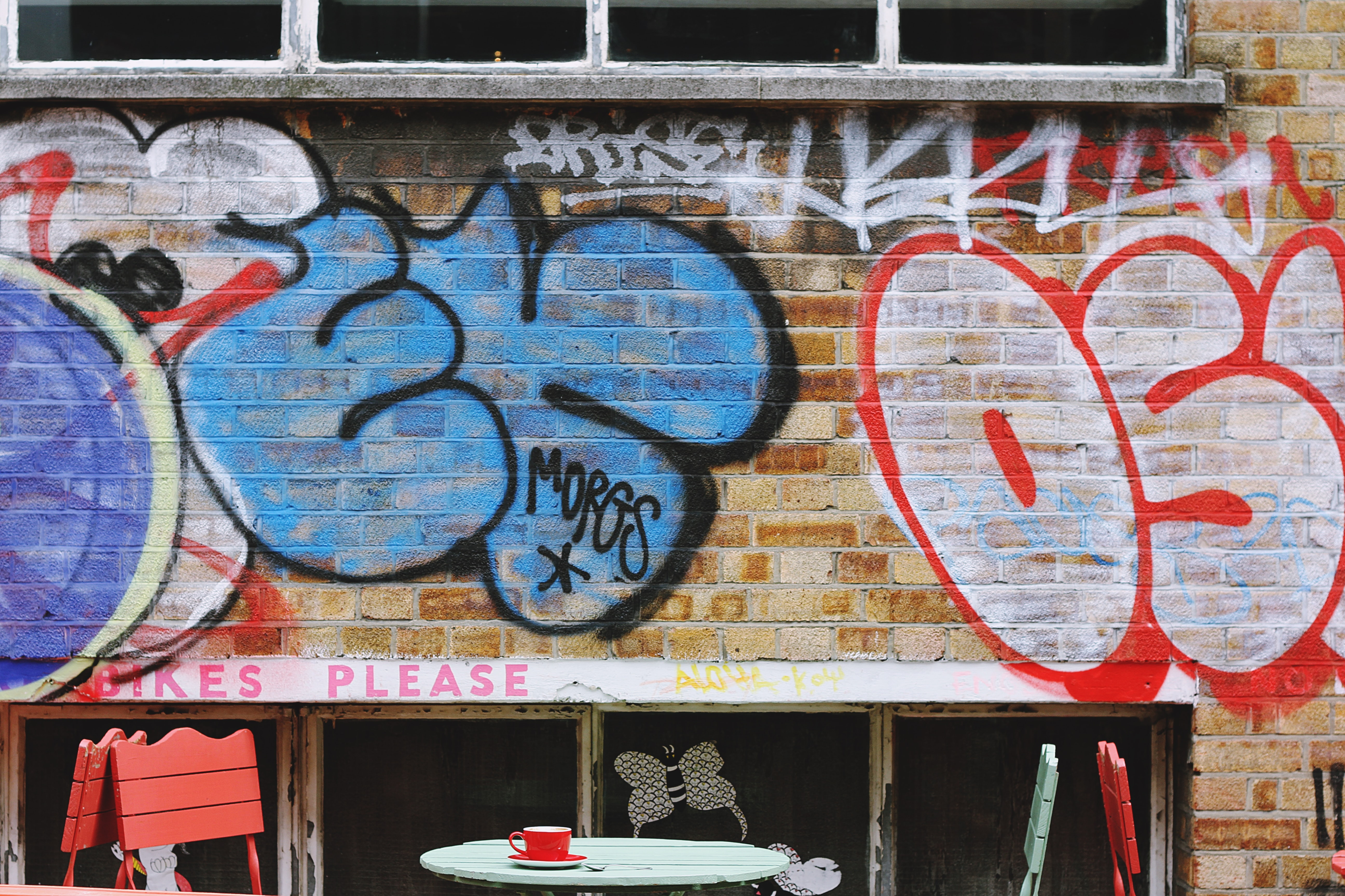 Grunge graffiti on brick wall behind colorful tables and chairs in Shoreditch
