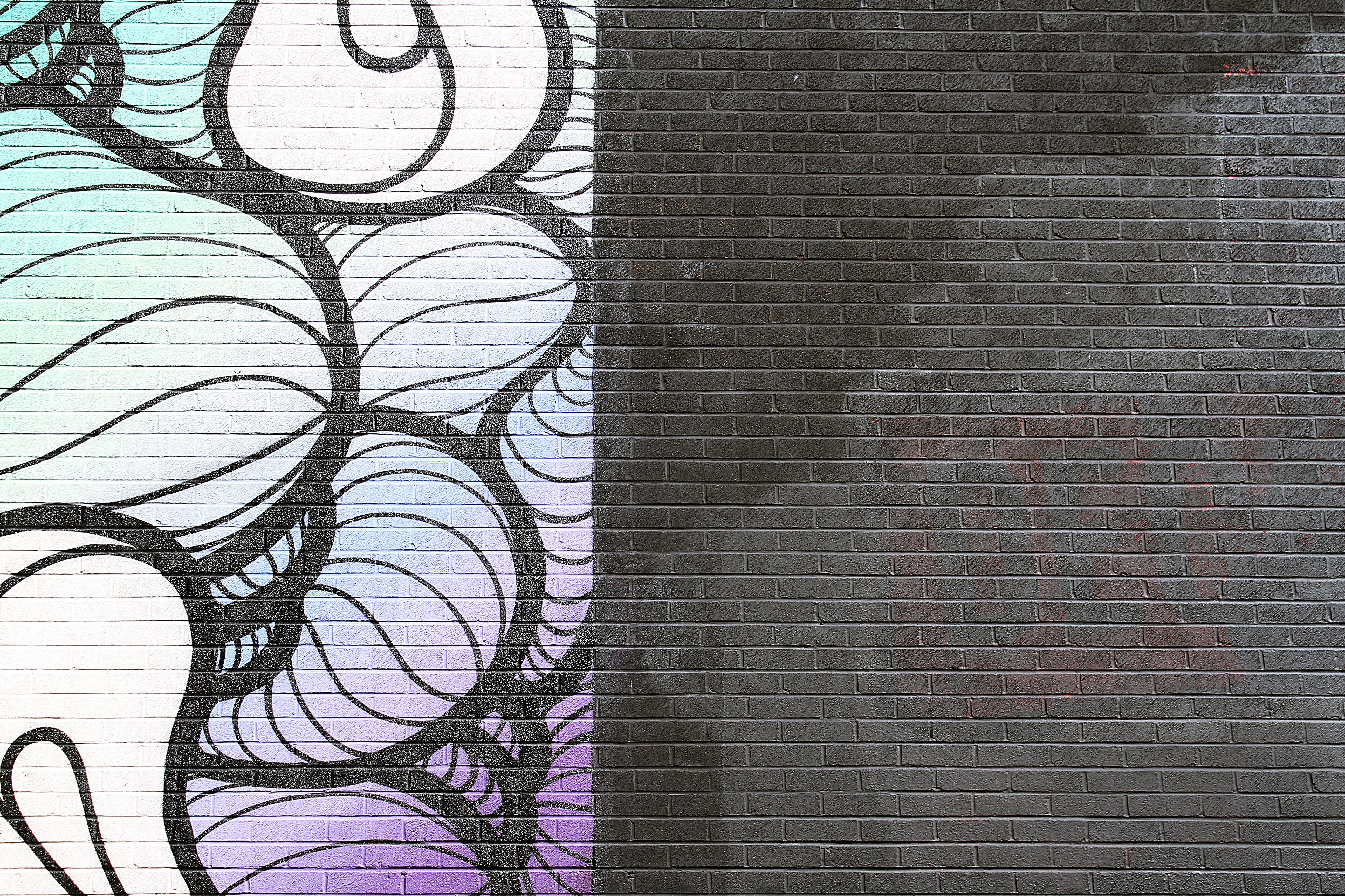 London wall painted half black with abstract mural on left half