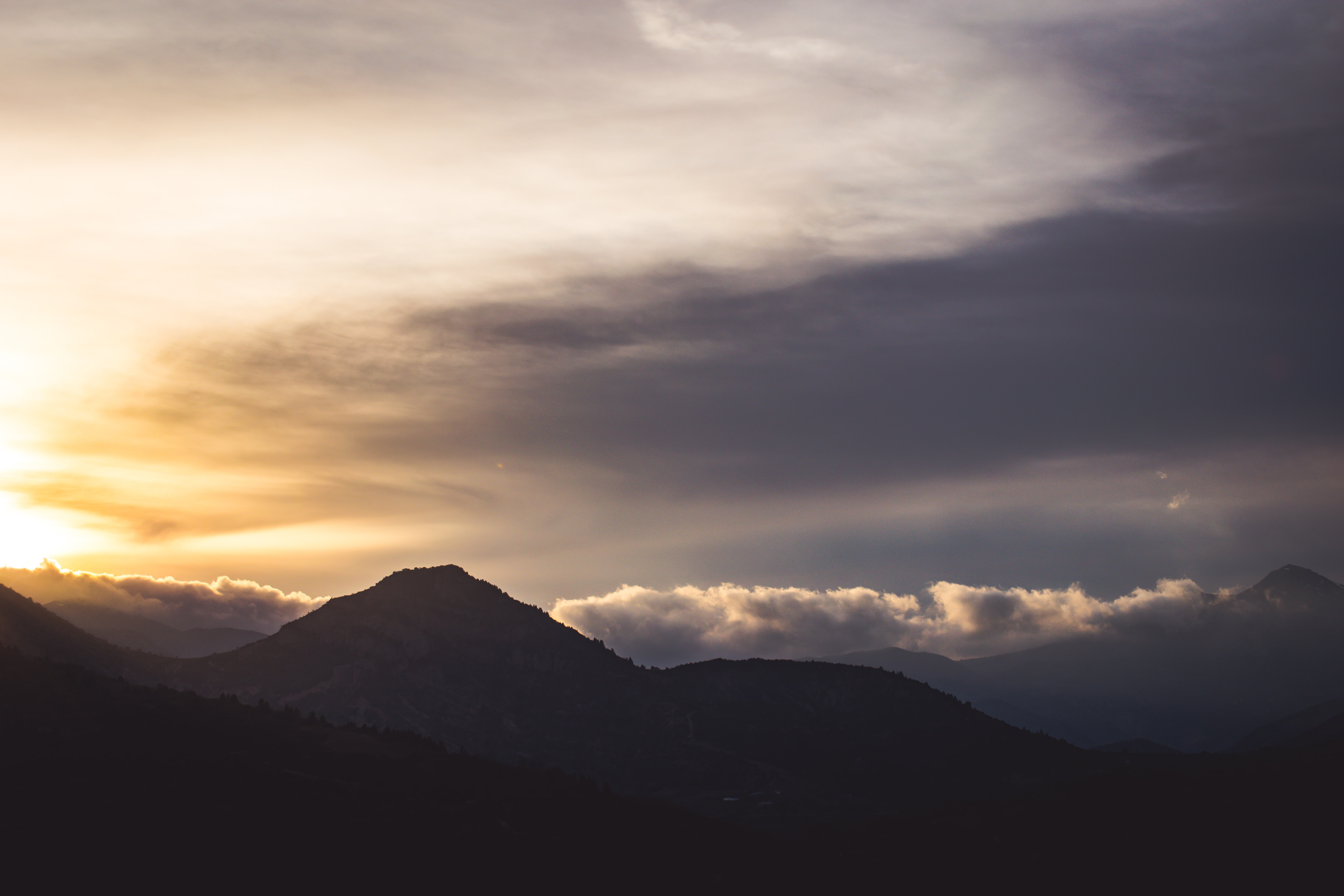 silhouette of mountain under cloudy sky at golden hour\