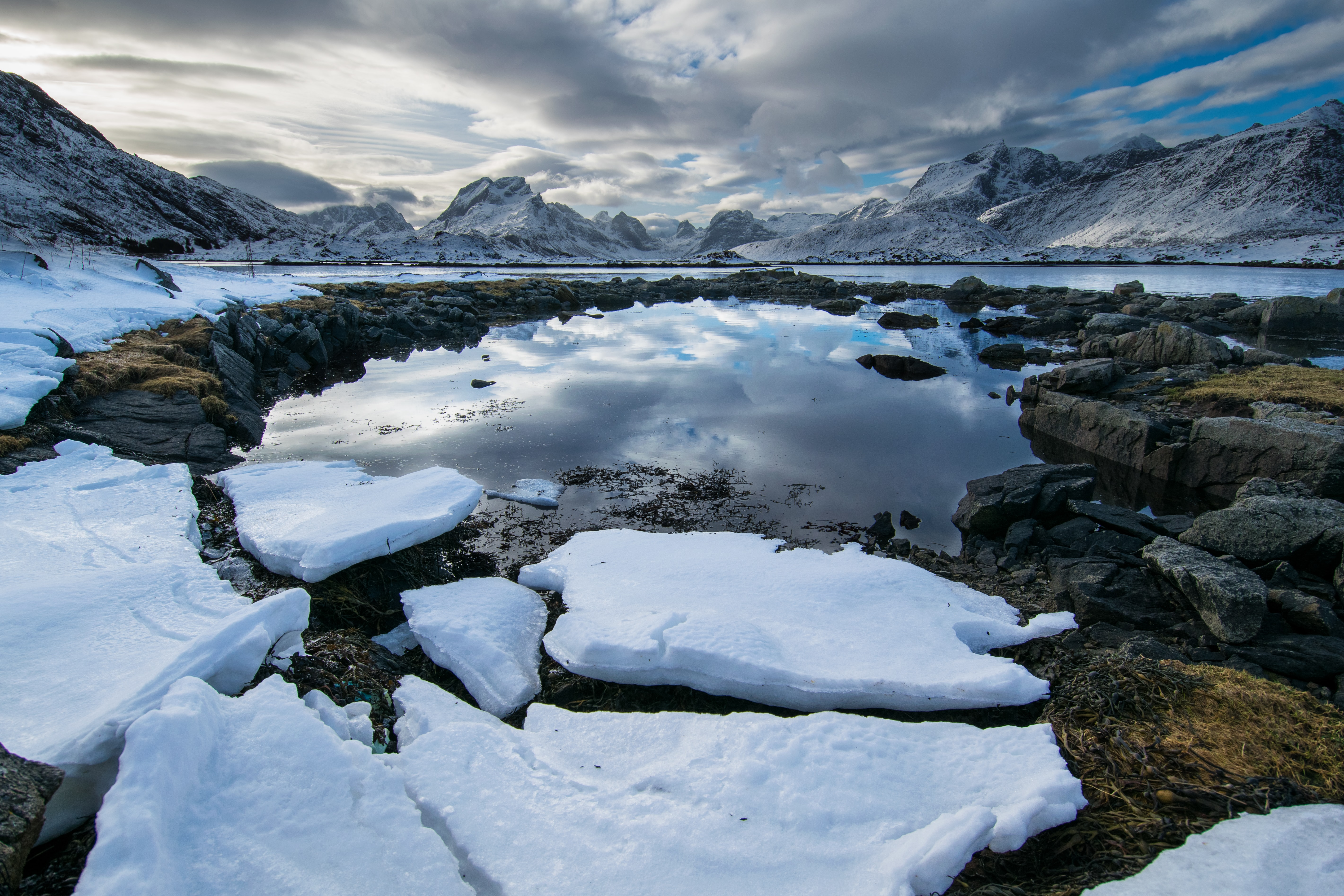 Snow patches along rocks around a lake near mountains, with cloud reflections in the water