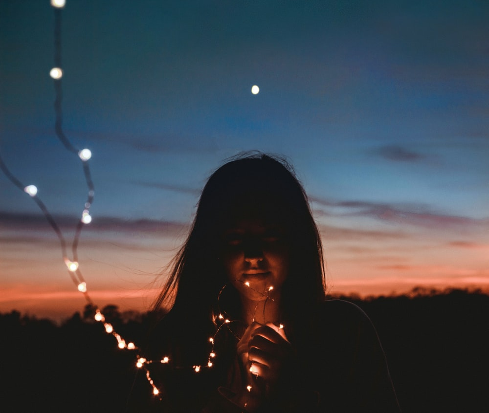 woman holding gold string lights