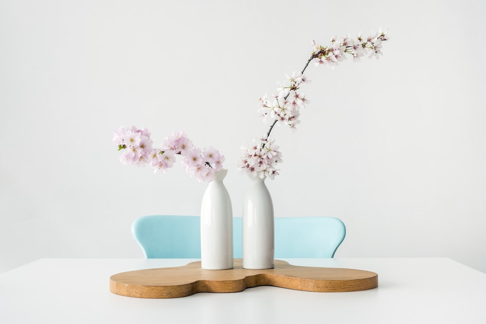 two pink petaled flowers in white vases on brown wooden surface