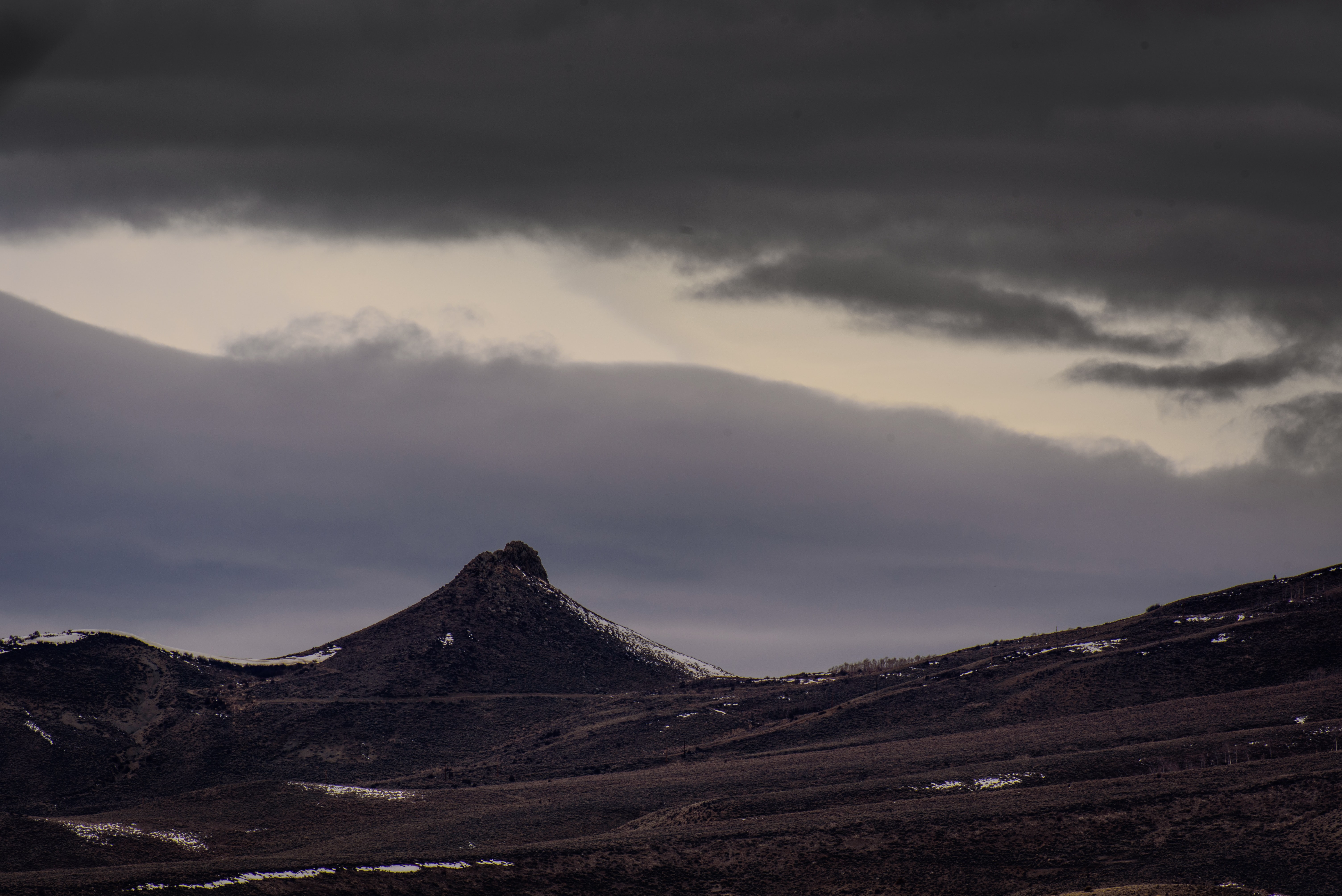 A jagged mountain peak crowns the horizon under thick clouds