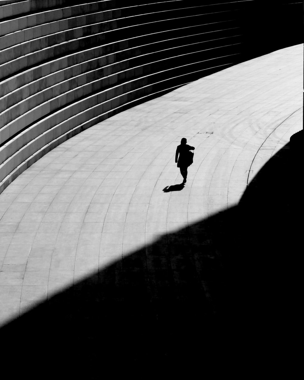 silhouette of a person walking on gray concrete floor