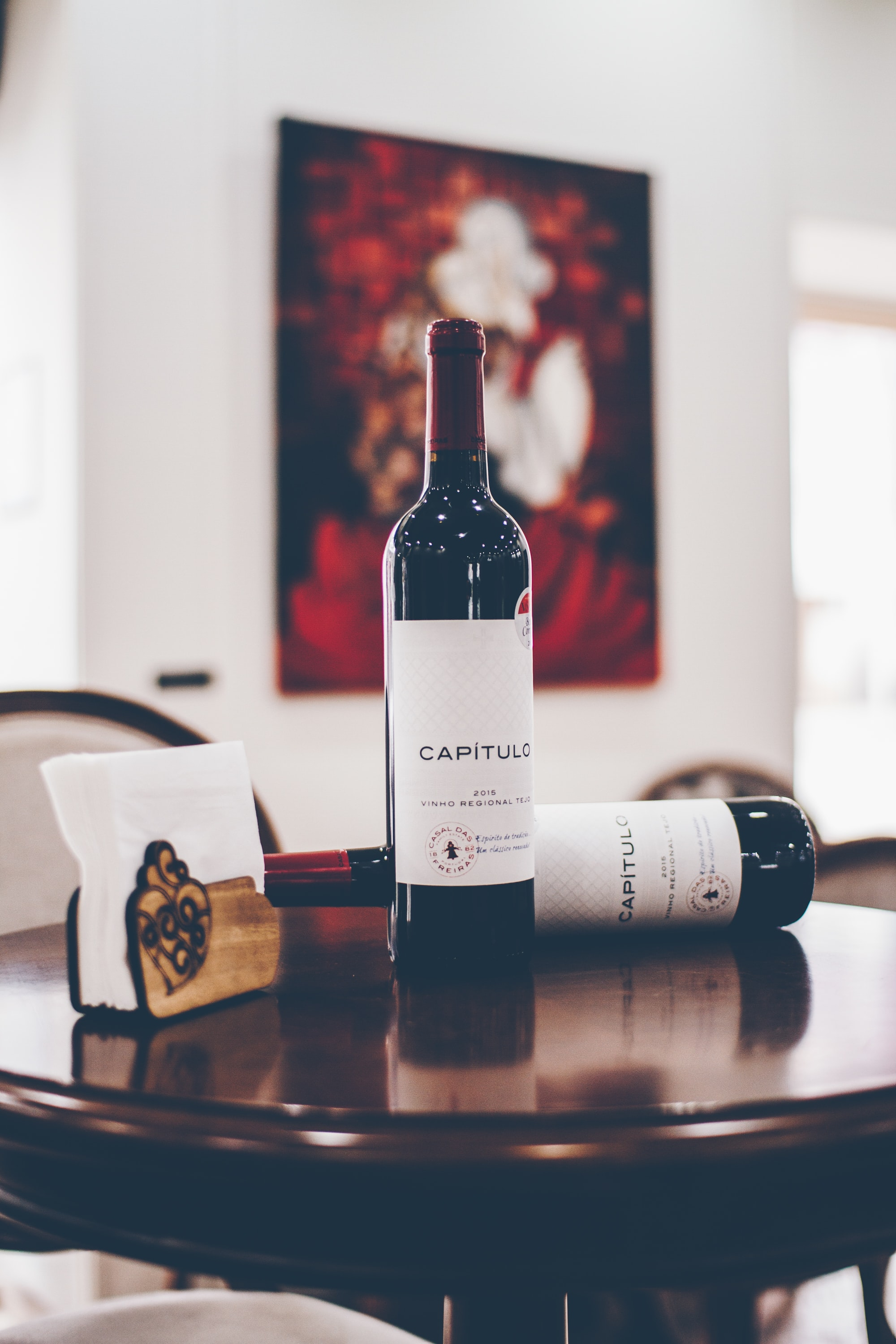 A bottle of red wine on a dining table.