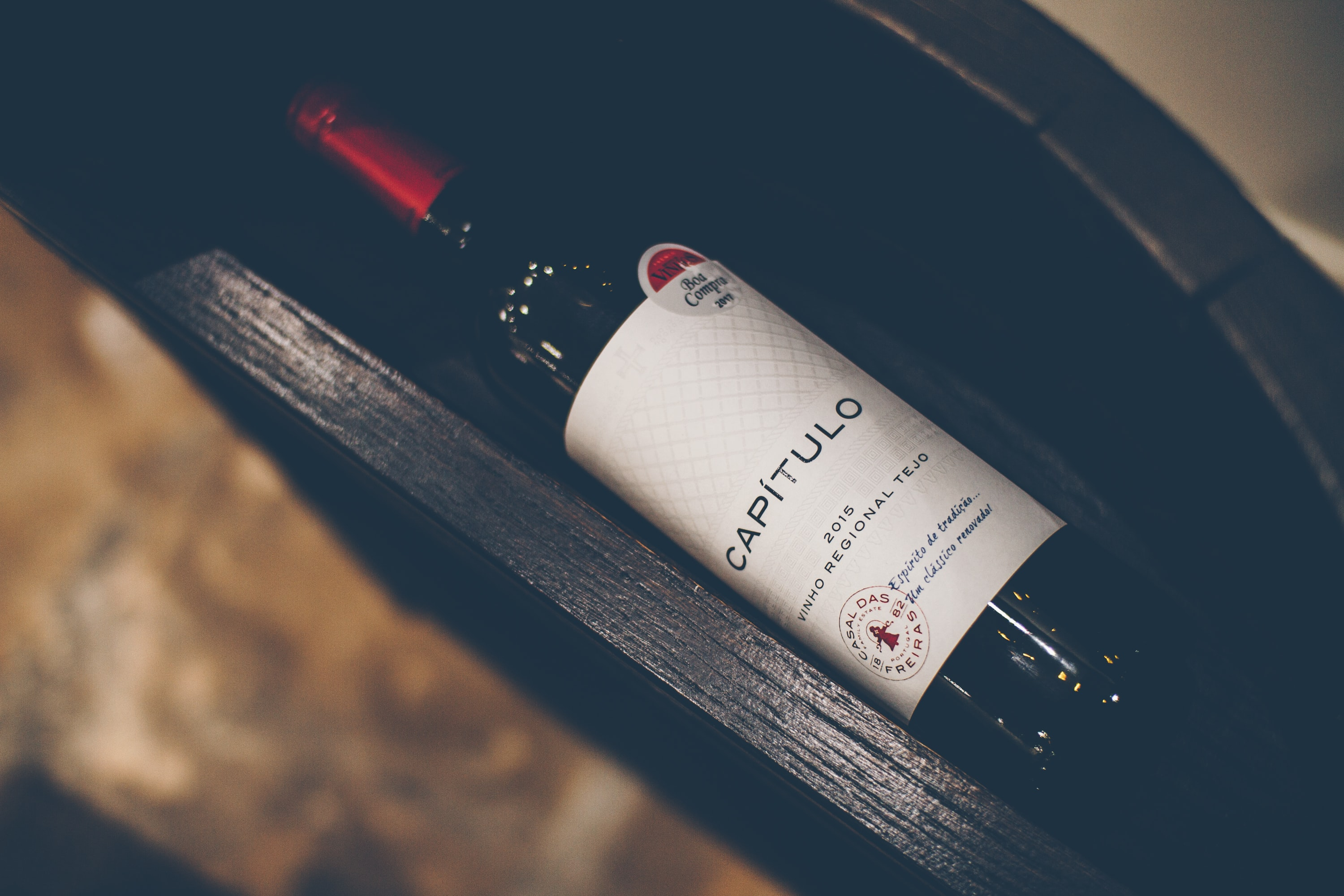 A bottle of unopened red wine inside a drawer.