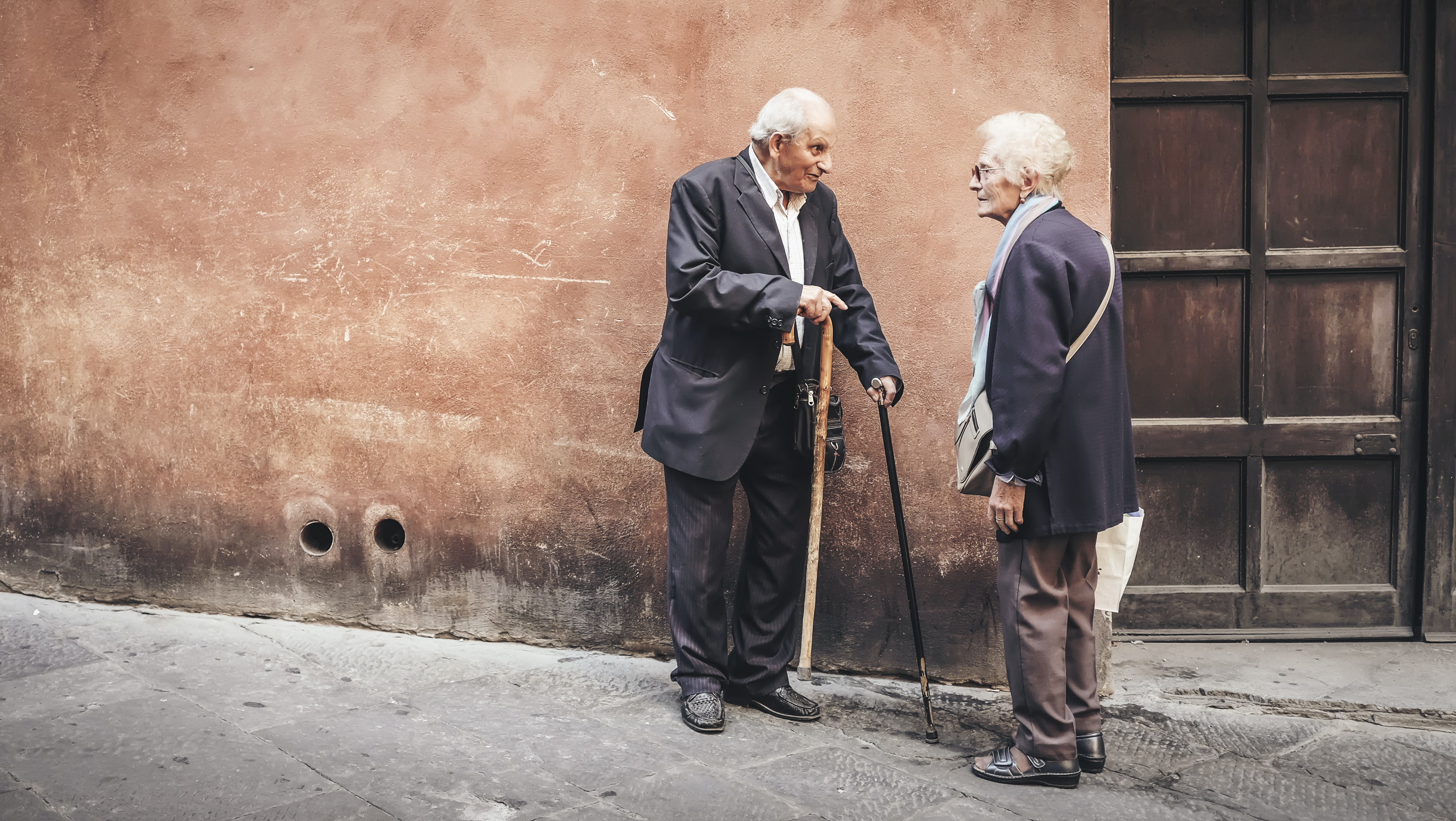 An old man and woman having a conversation with their canes next to a doorway.