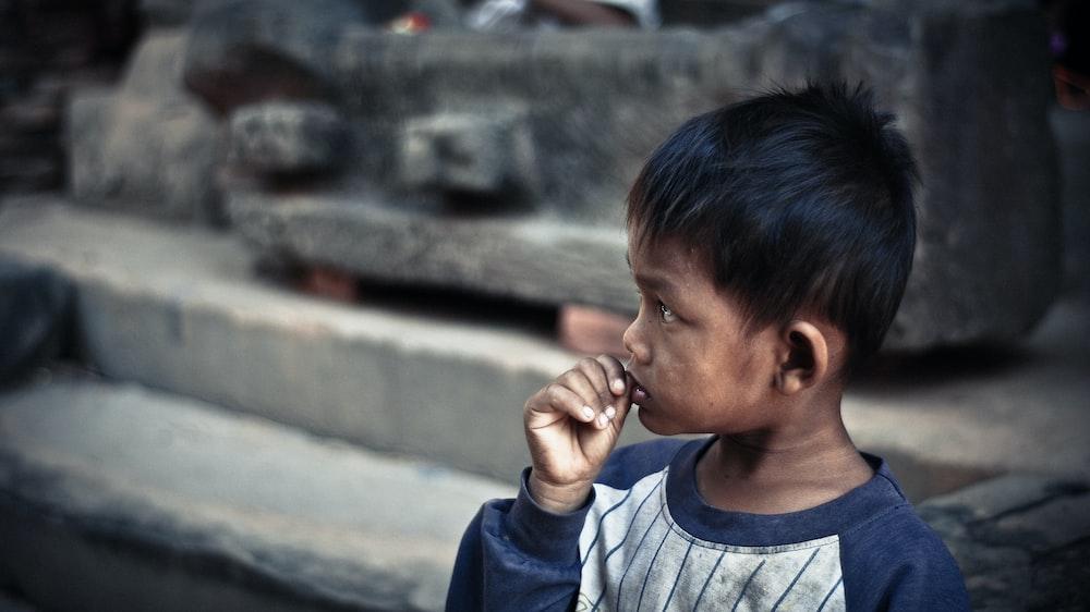 boy holding his lip standing on sidewalk