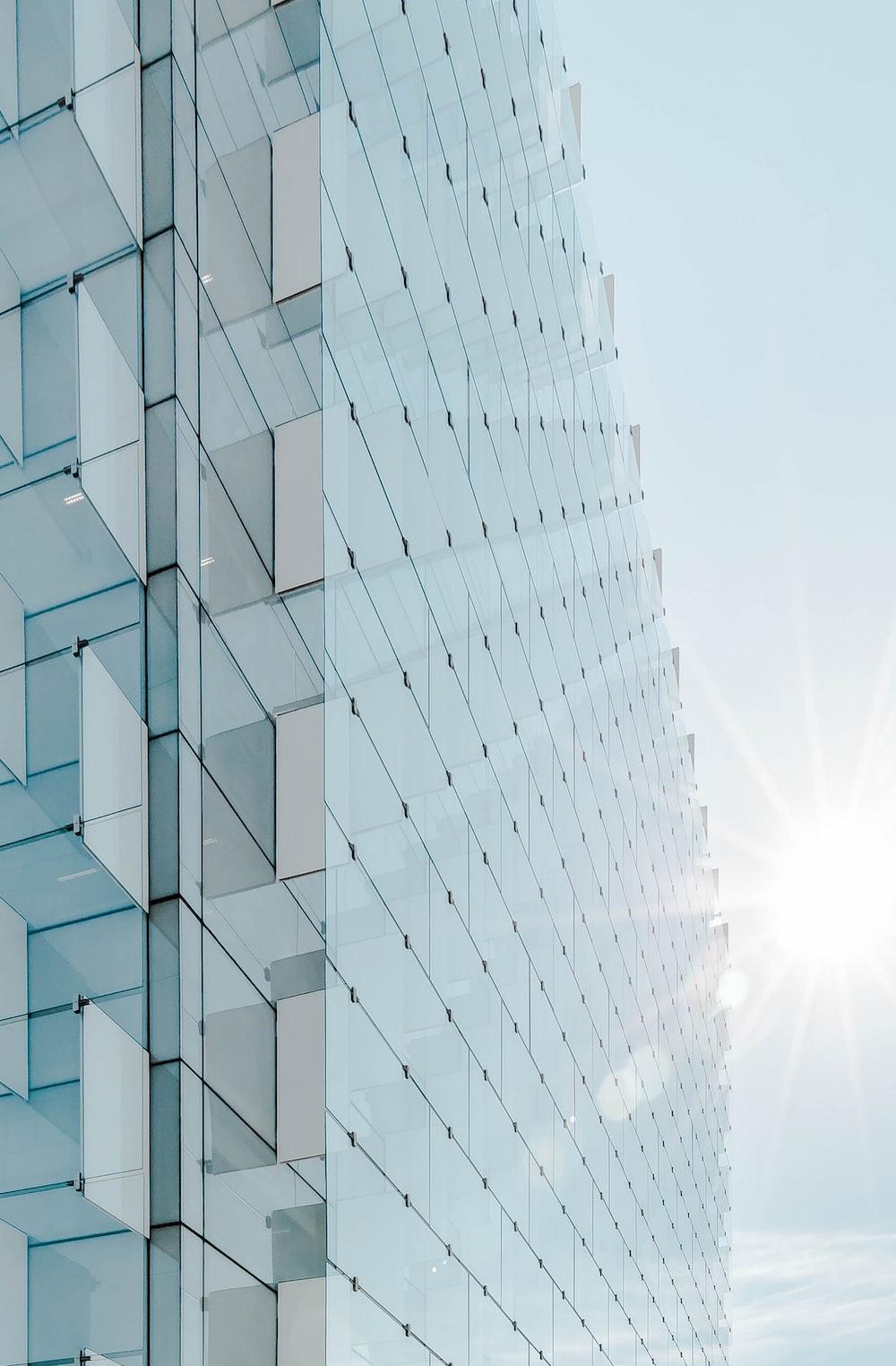 glass panel high-rise building under blue sky with sun raise