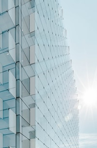 glass panel high-rise building under blue sky with sun raise