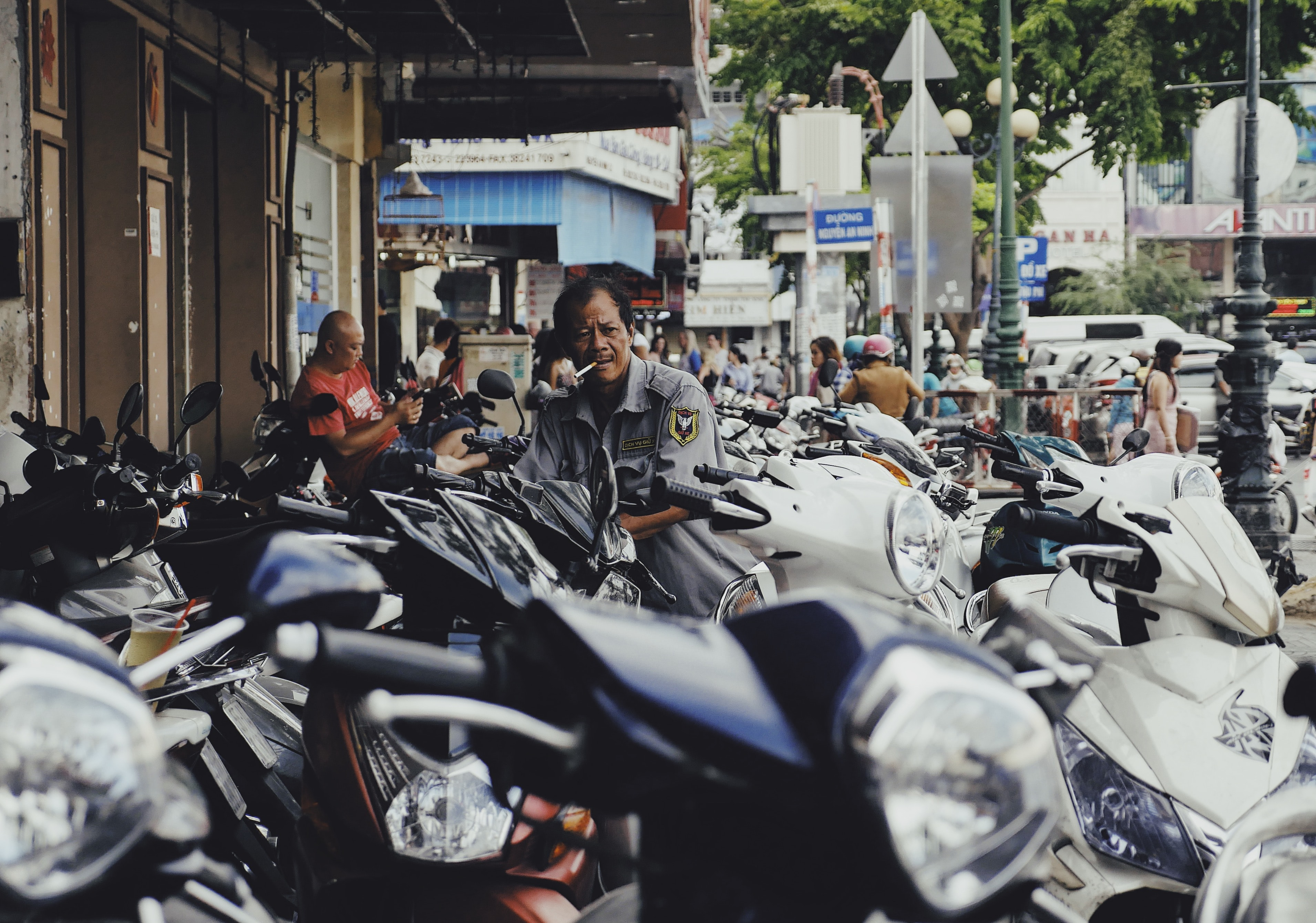 A man smokes a cigarette while standing among an array of motor scooters in the city