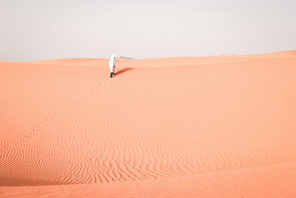 person walking on desert during daytime