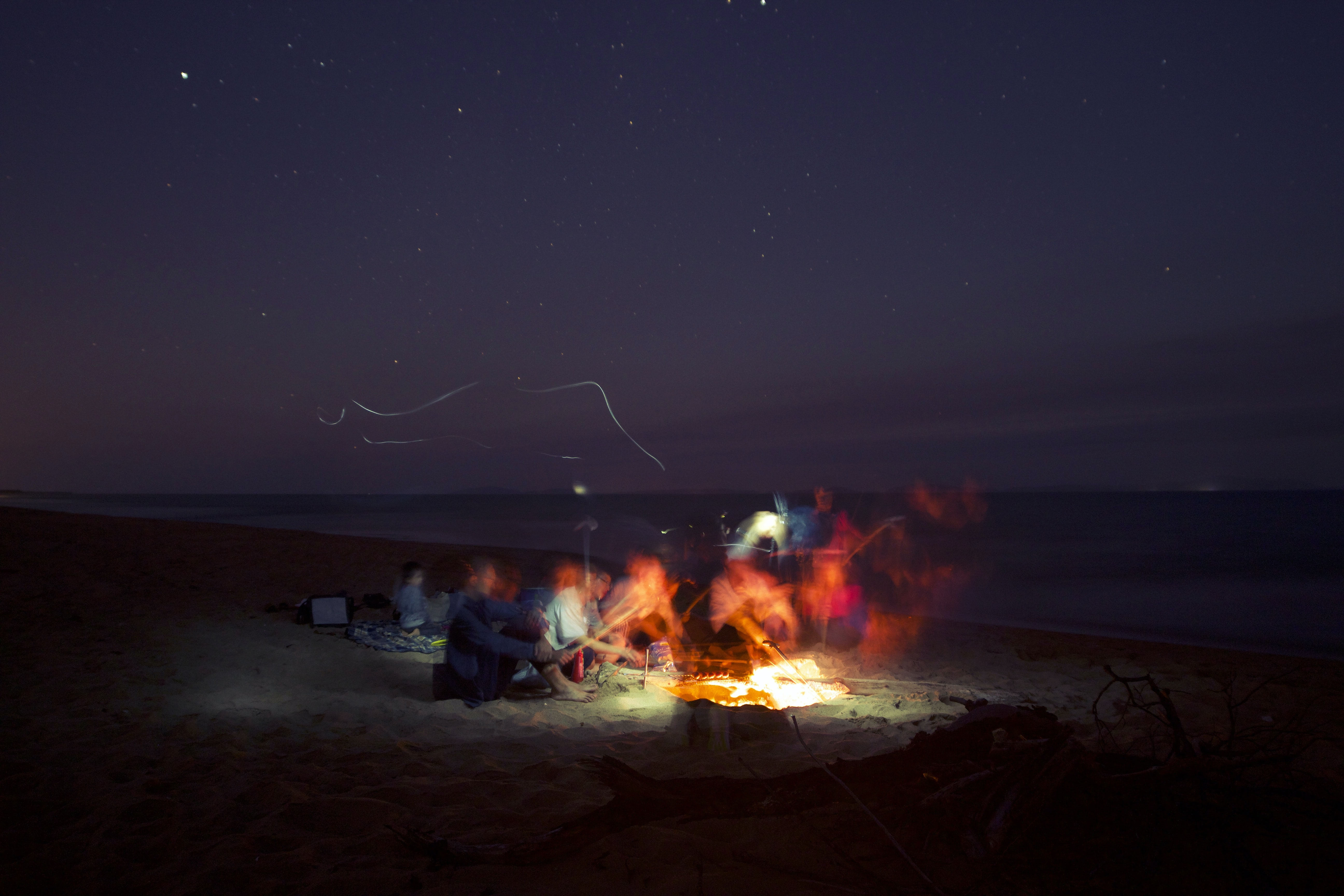 Long exposure of a group of friends hanging around a beach bonfire lighting the dark night