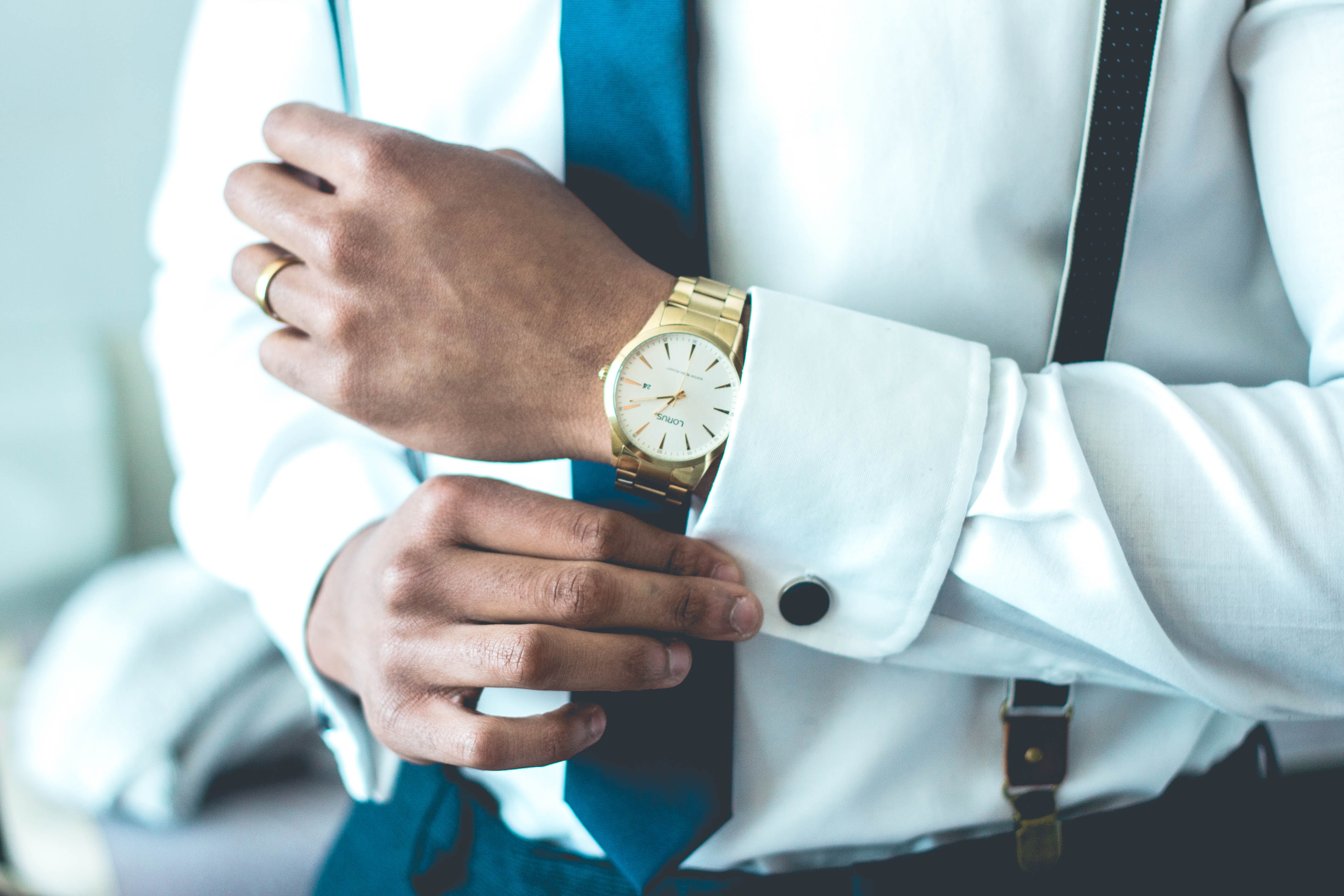 A man in a gold watch adjusting the cuffs of his white shirt