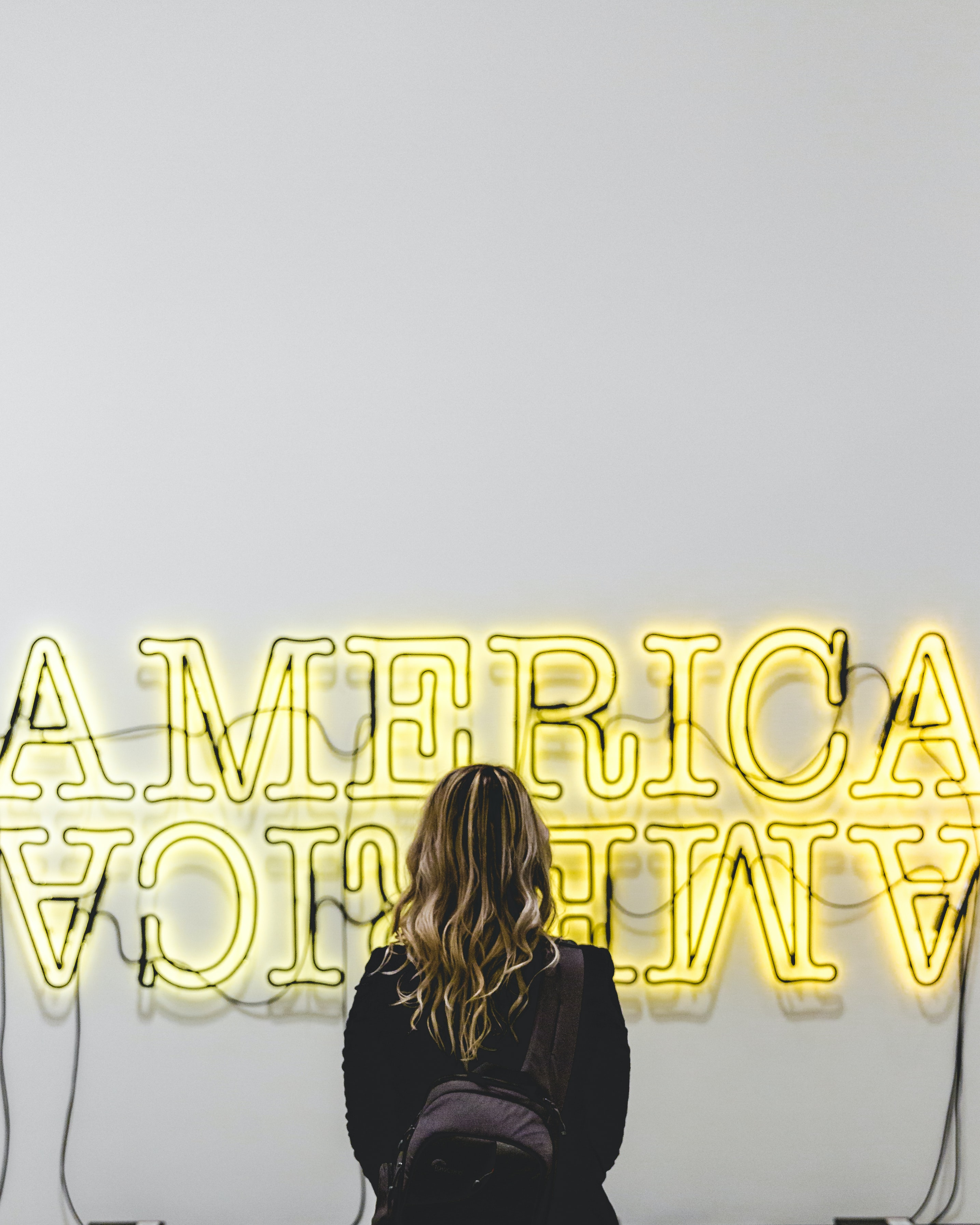 A long-haired woman stares at a neon sign at The Broad, a museum in Los Angeles, California