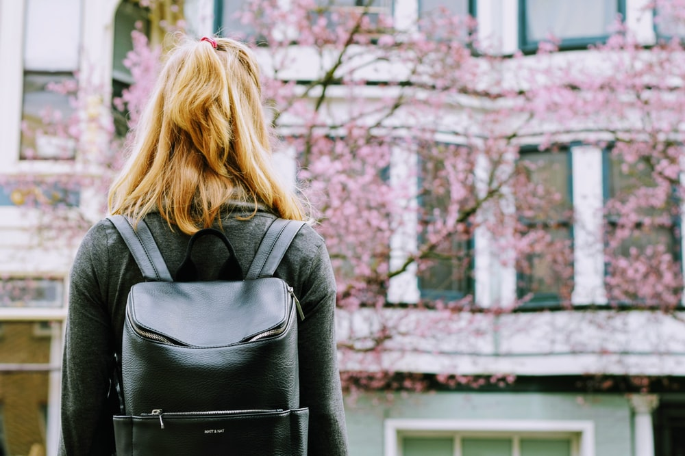woman wearing backpack facing concrete building