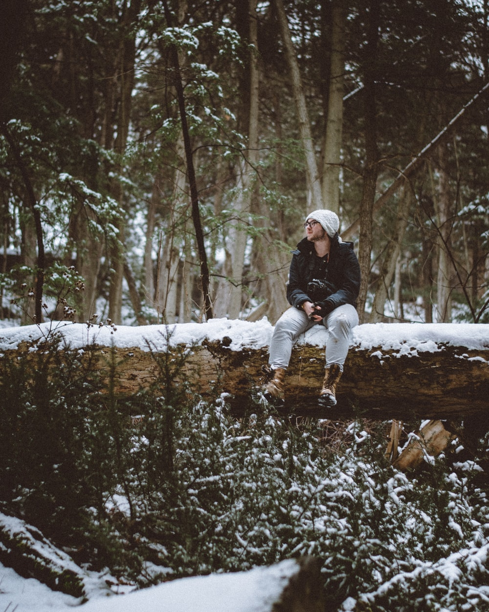 man wearing white knit cap and black jacket sitting on snow covered tree log