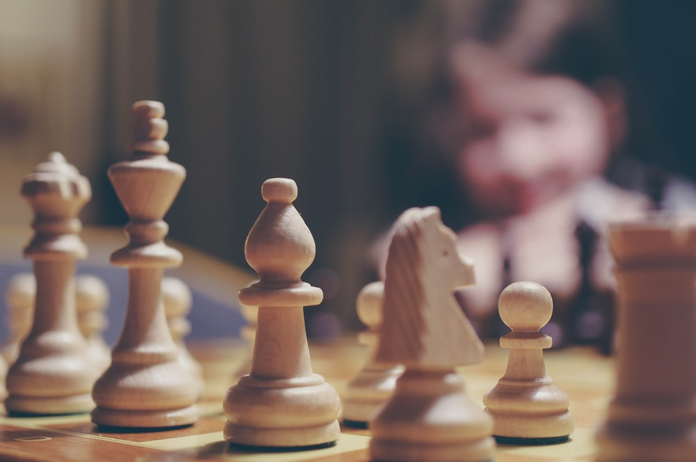 beige chess piece on board in selective focus photography