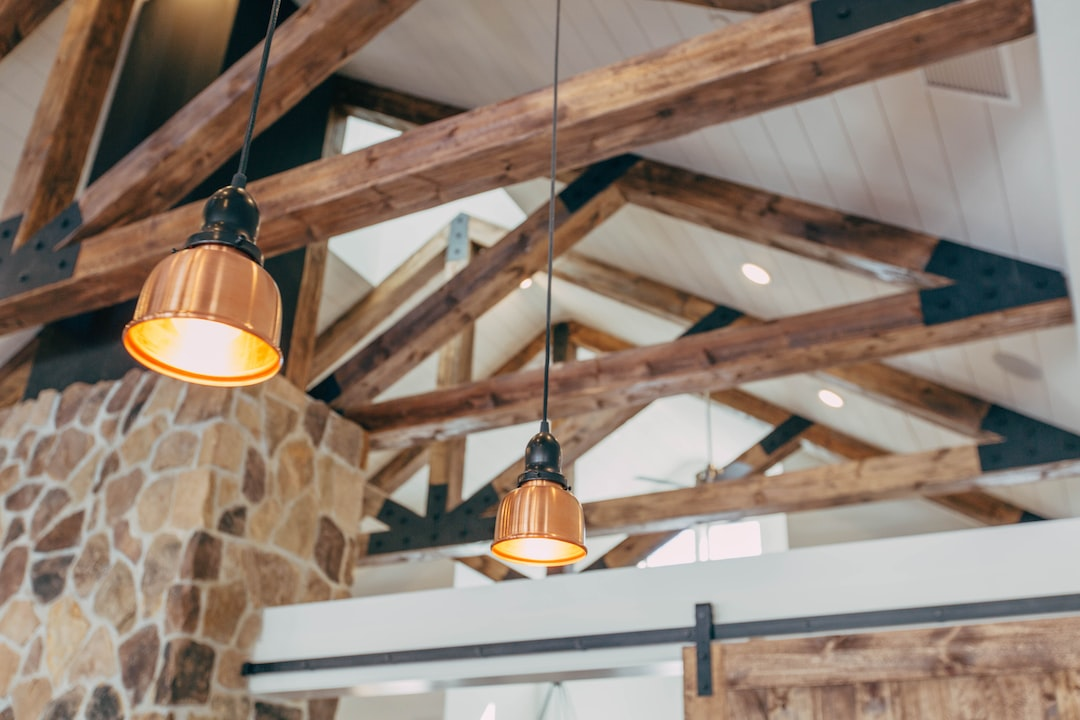 Ceiling of a house with wooden beams and rafters exposed and hanging lights between the rafters