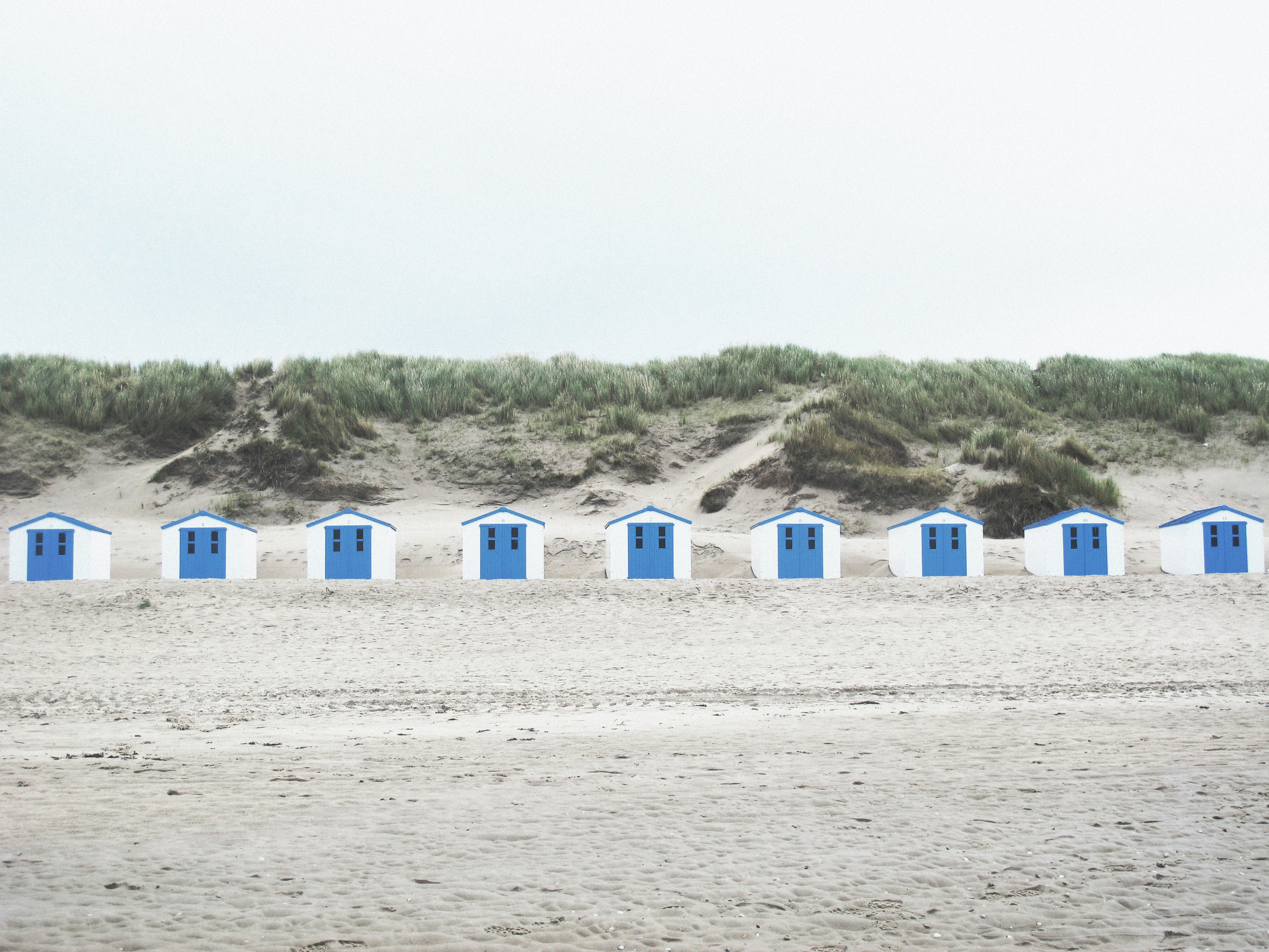 Blue and white beach huts on a sandy beach in New York, Texas