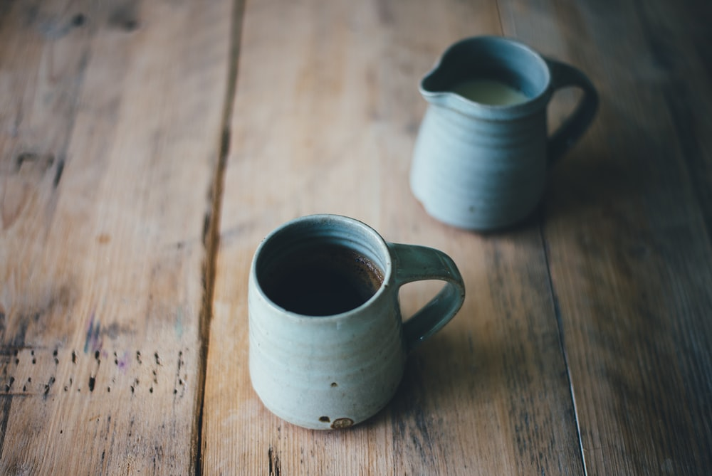 white ceramic mug with brown and white liquid inside on brown wooden surface