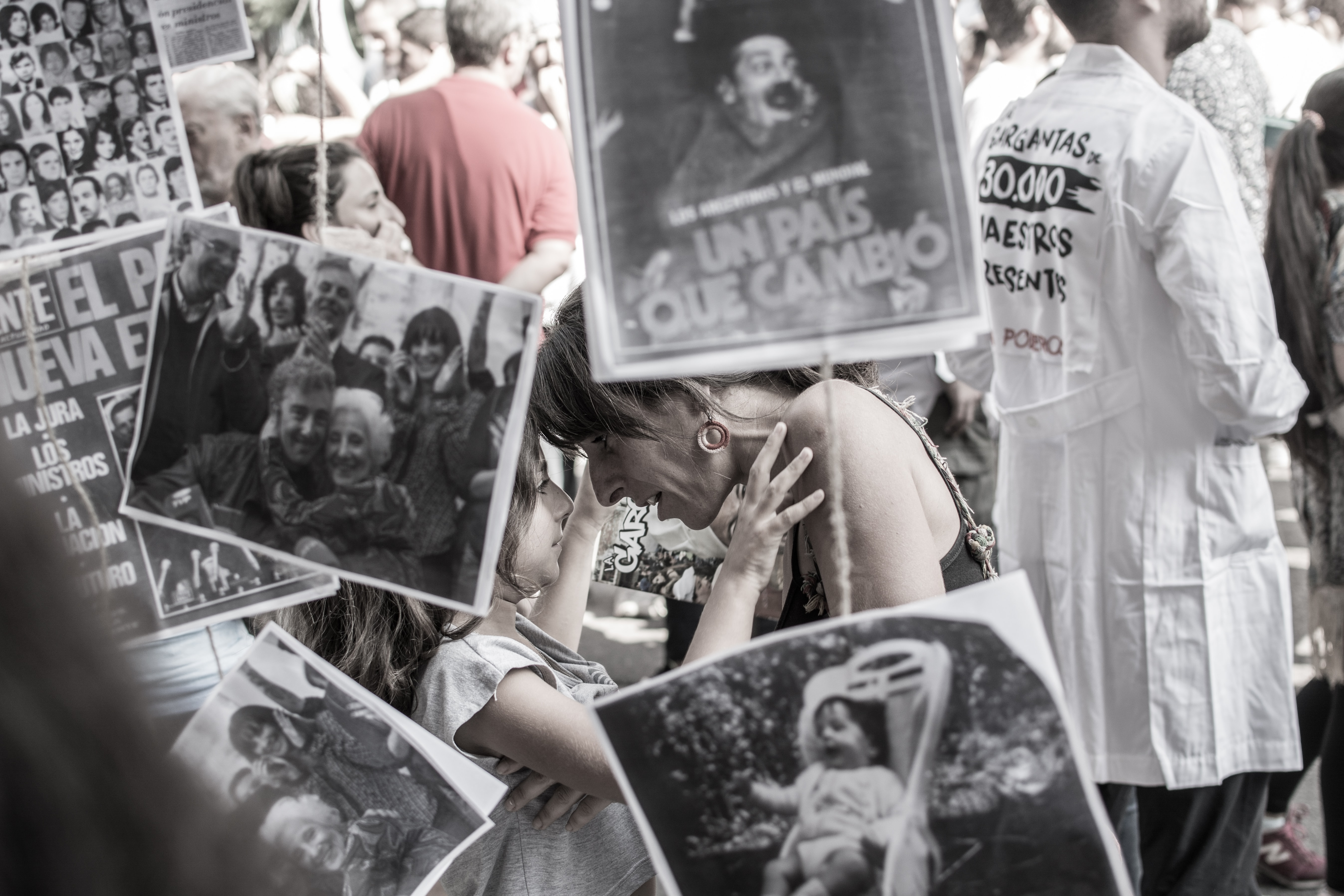A mother speaks to her daughter in a crowd full of protest signs in Buenos Aires